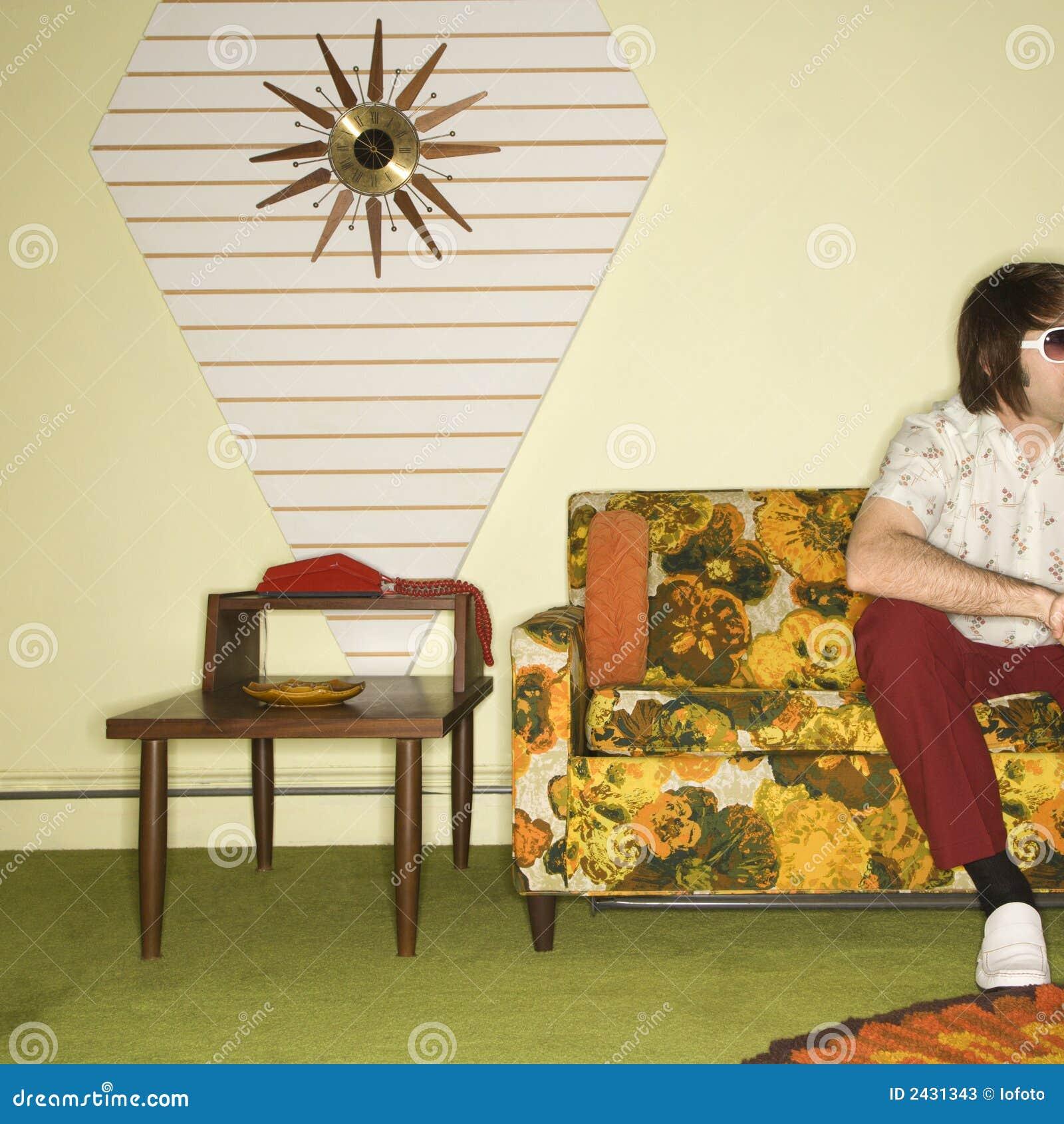 Homem que senta-se no sofá.