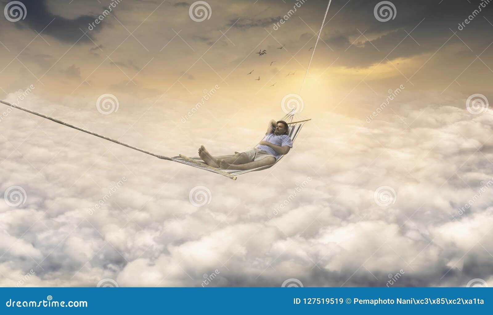 Homem que sonha na rede de balanço acima do céu