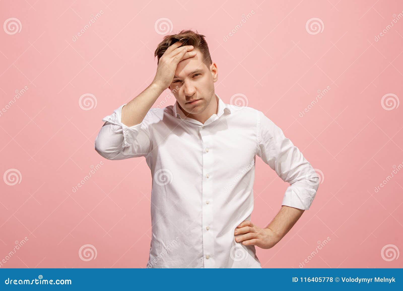 Homem que tem a dor de cabeça Isolado sobre o fundo cor-de-rosa
