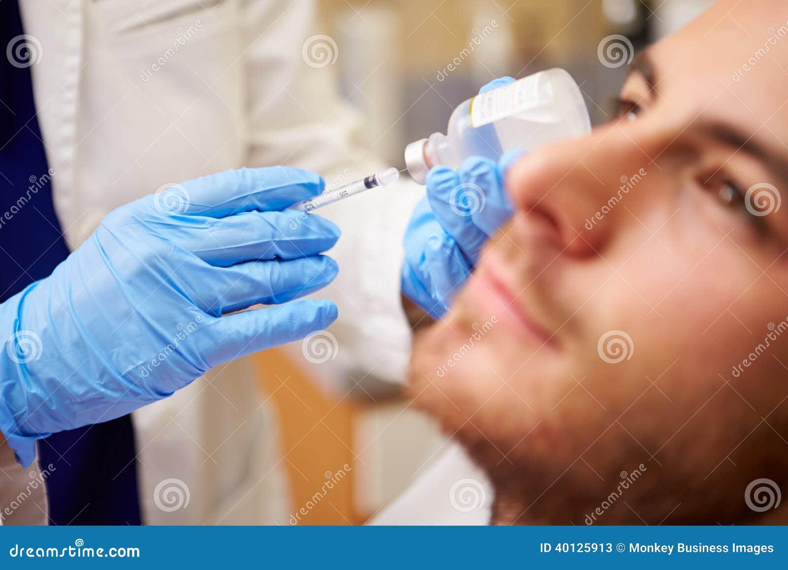 Homem que tem o tratamento de Botox na clínica da beleza