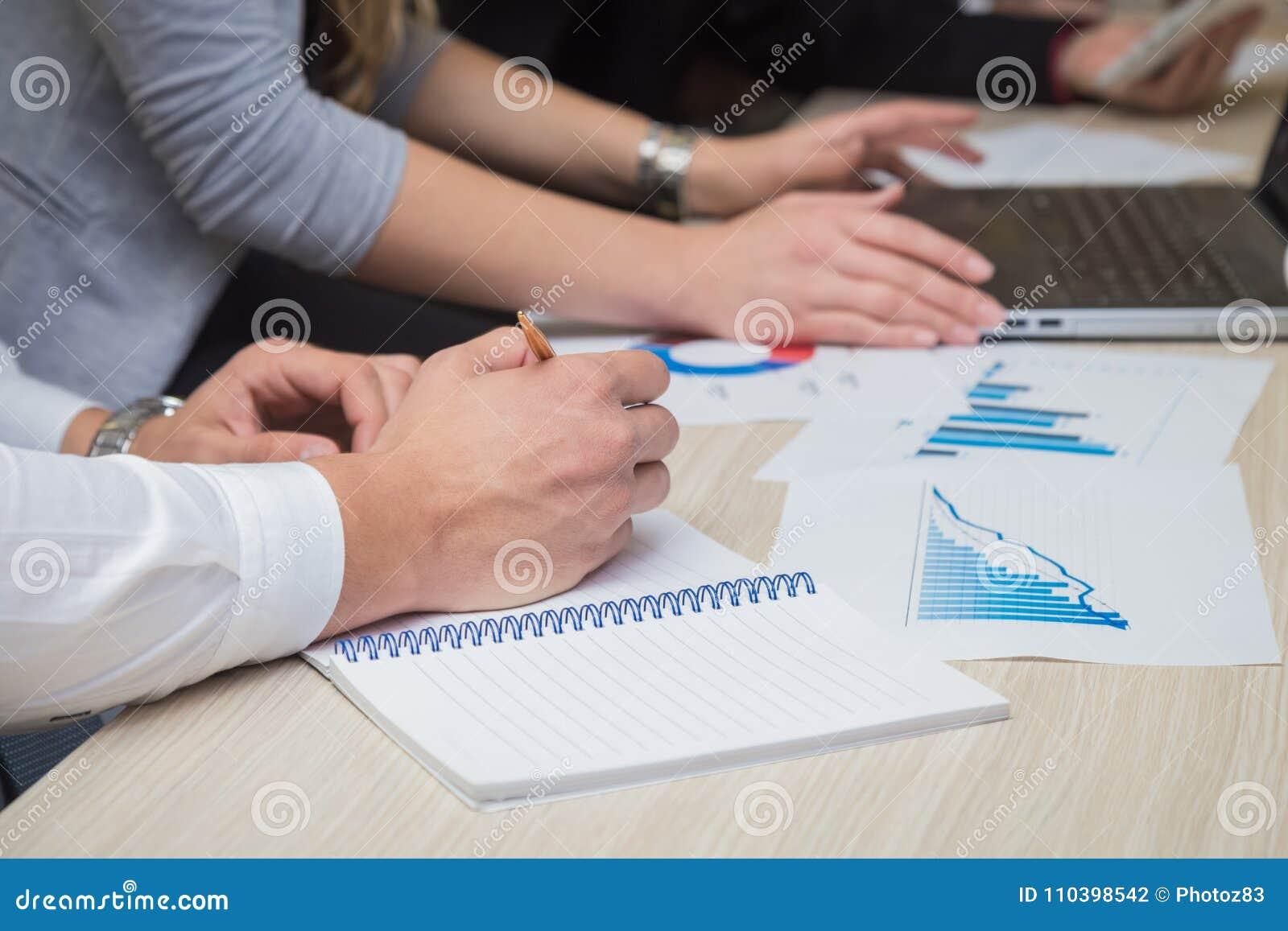 Homem que toma notas durante a reunião