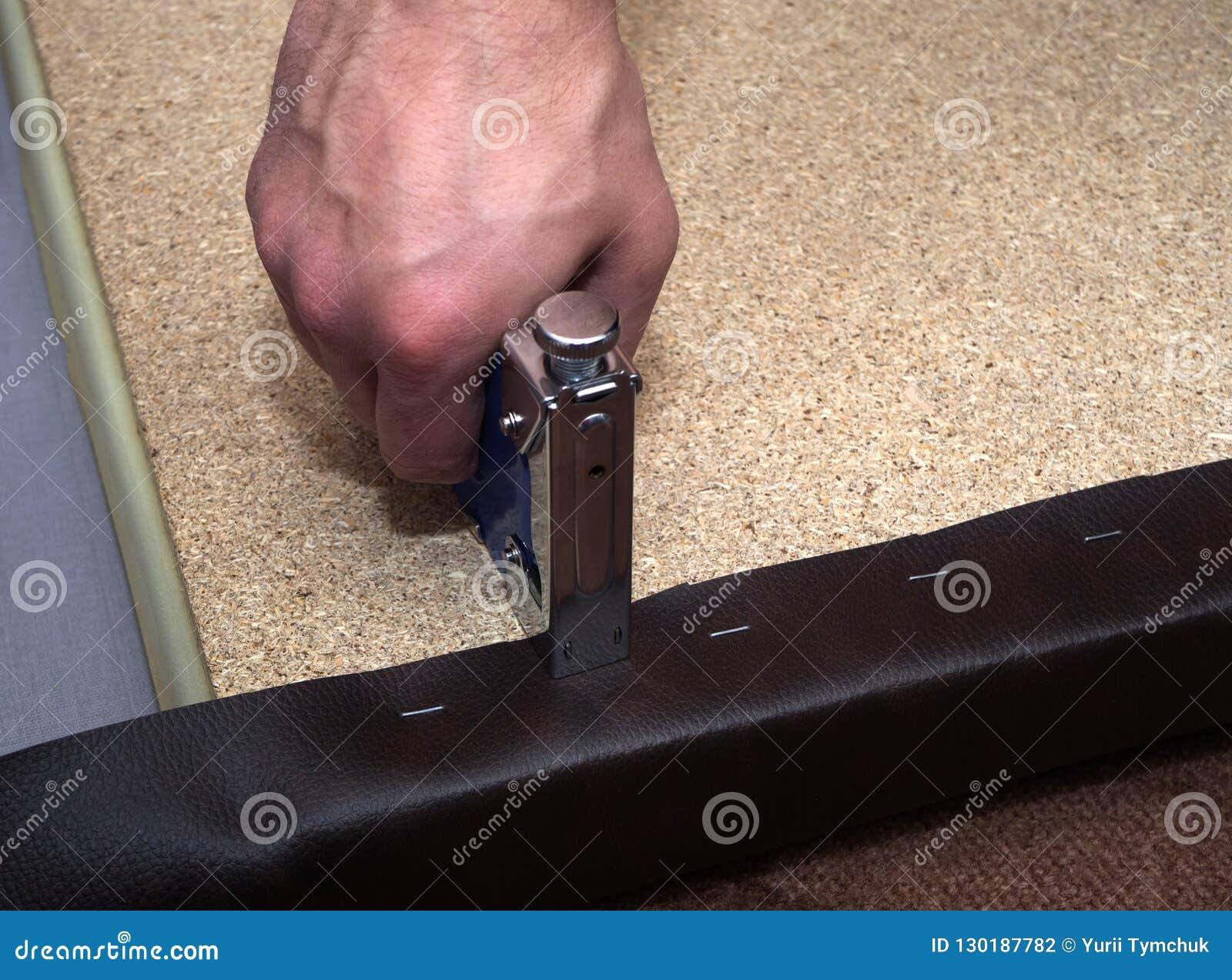 Homem que usa o grampeador da ferramenta e a placa de partícula de estofamento do couro sintético