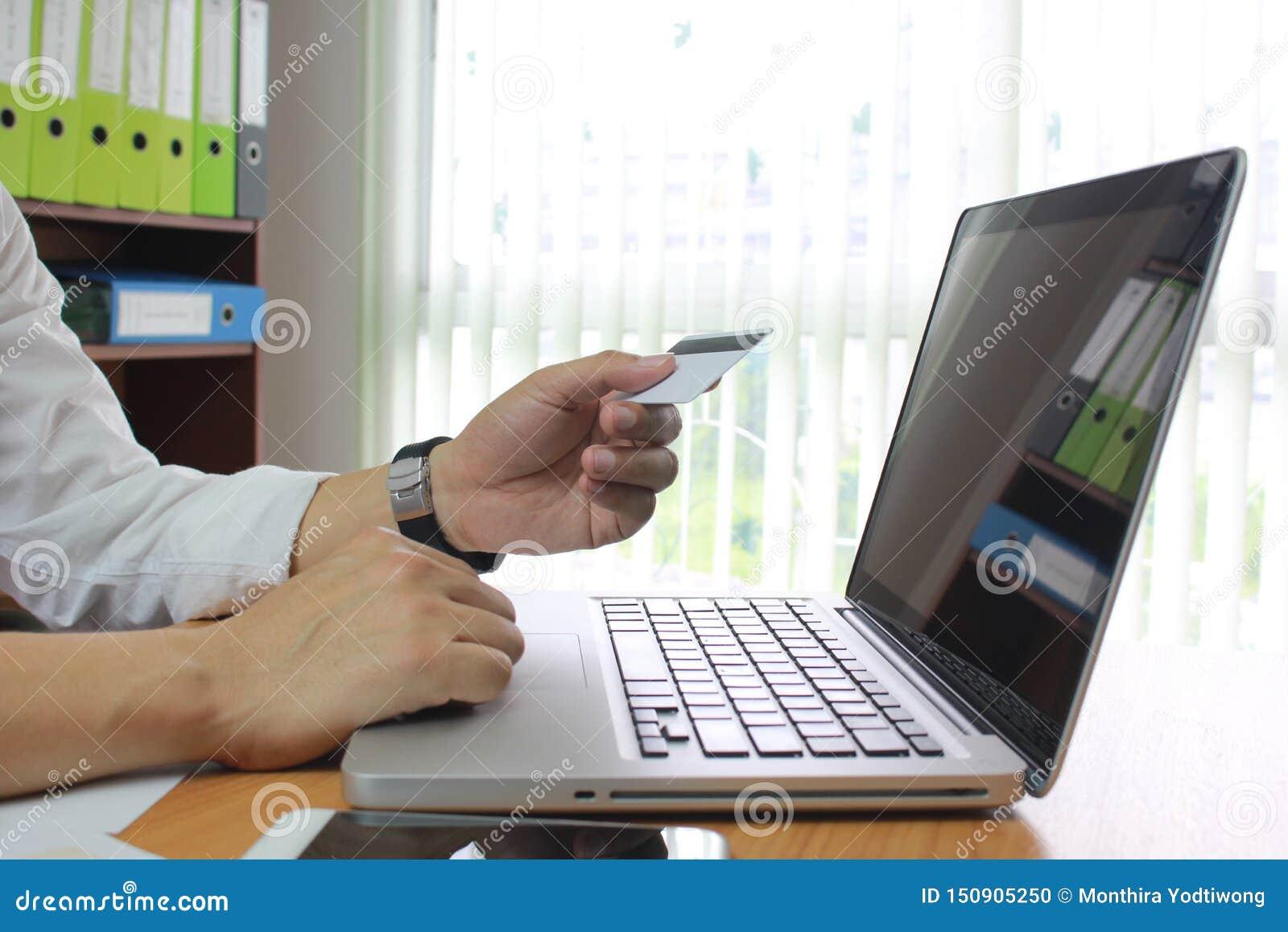 Homem que usa o portátil e as mãos que guardam o cartão de crédito, conceito em linha do pagamento
