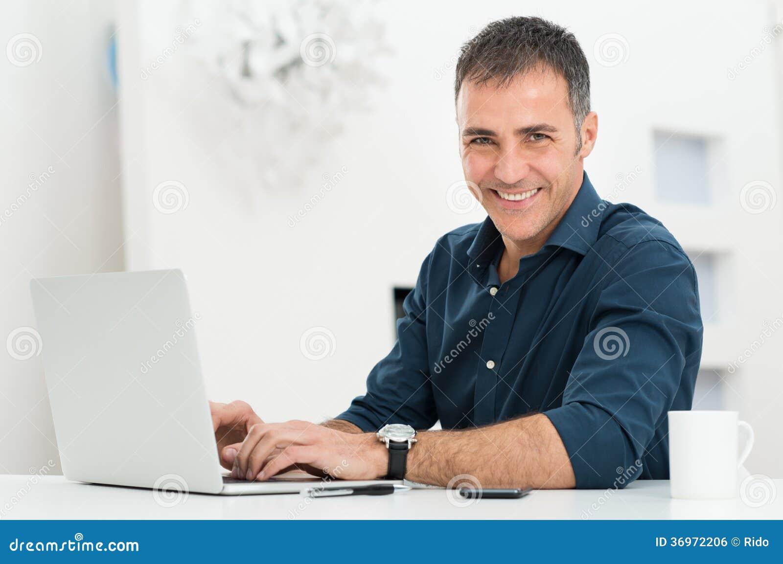 Homem que usa o portátil na mesa