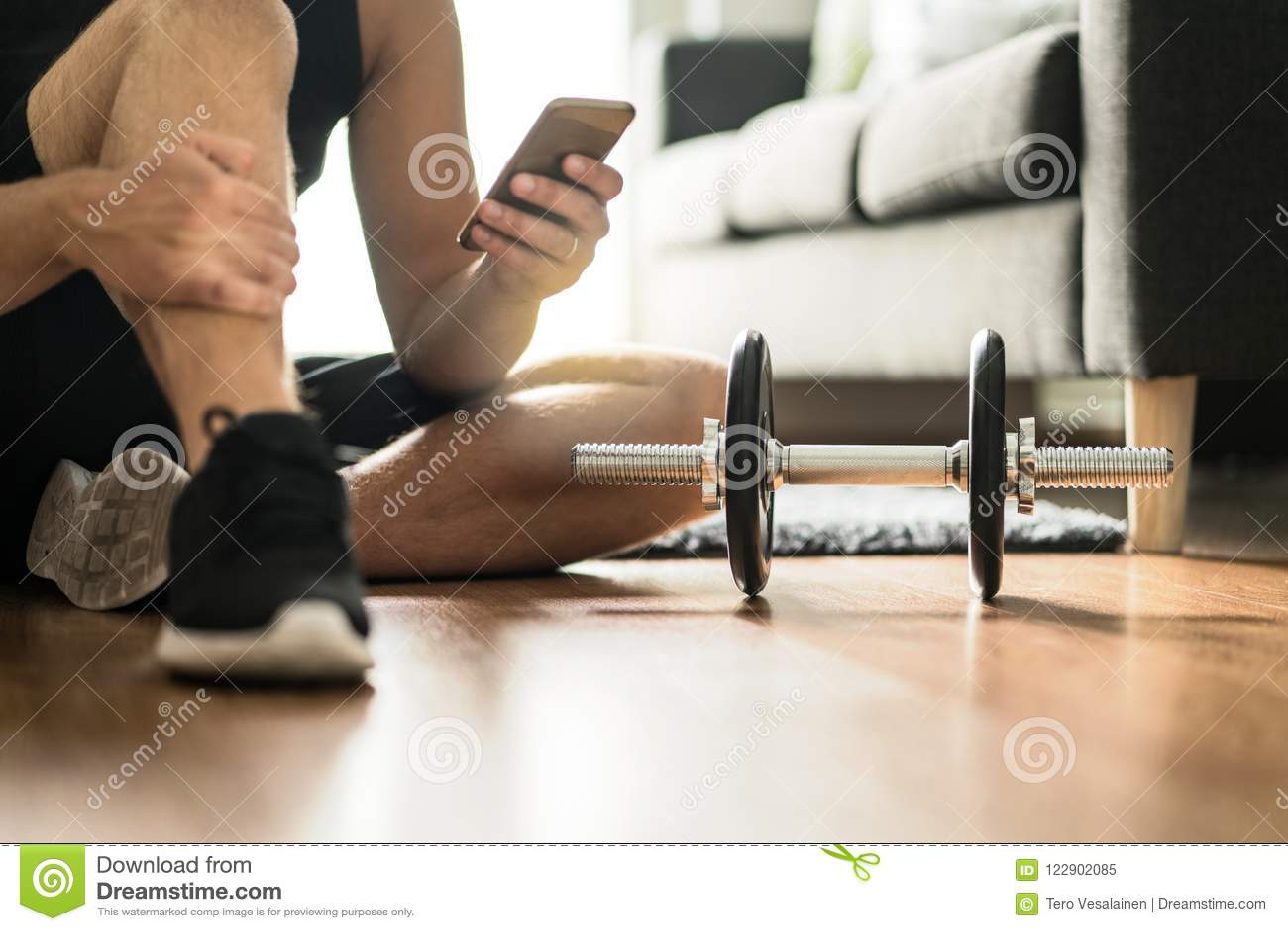 Homem que usa o smartphone durante o exercício em casa