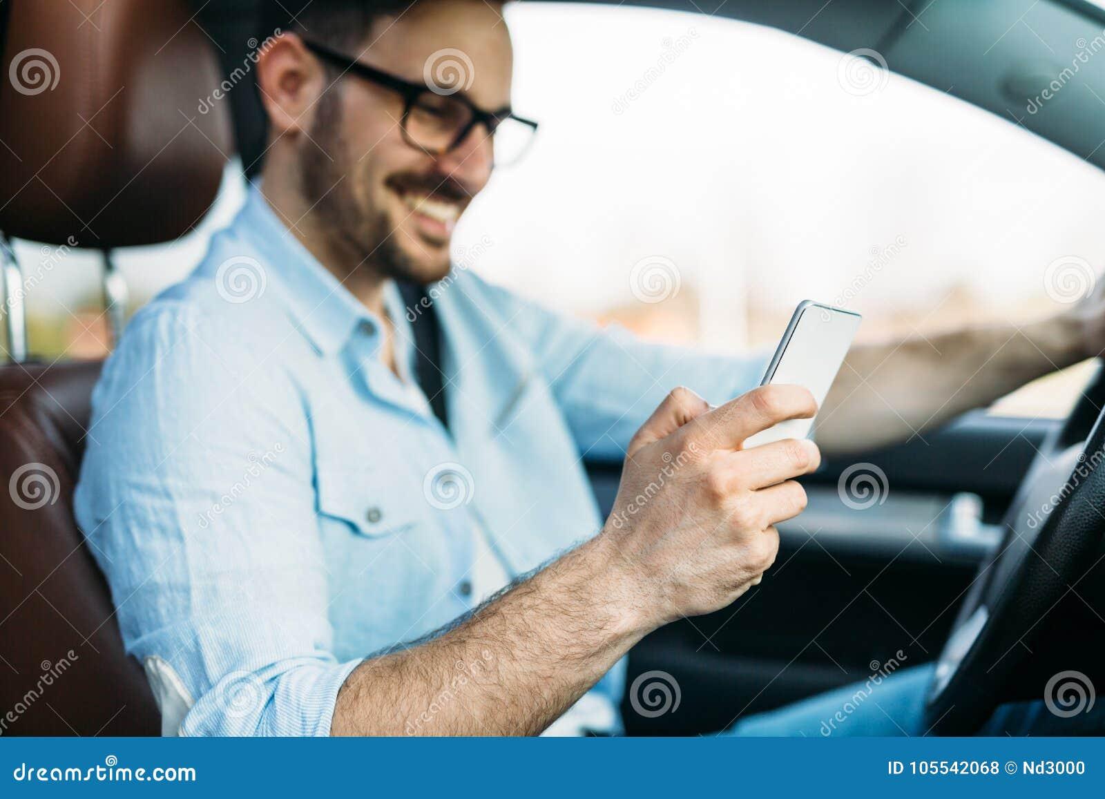 Homem que usa o telefone ao conduzir o carro