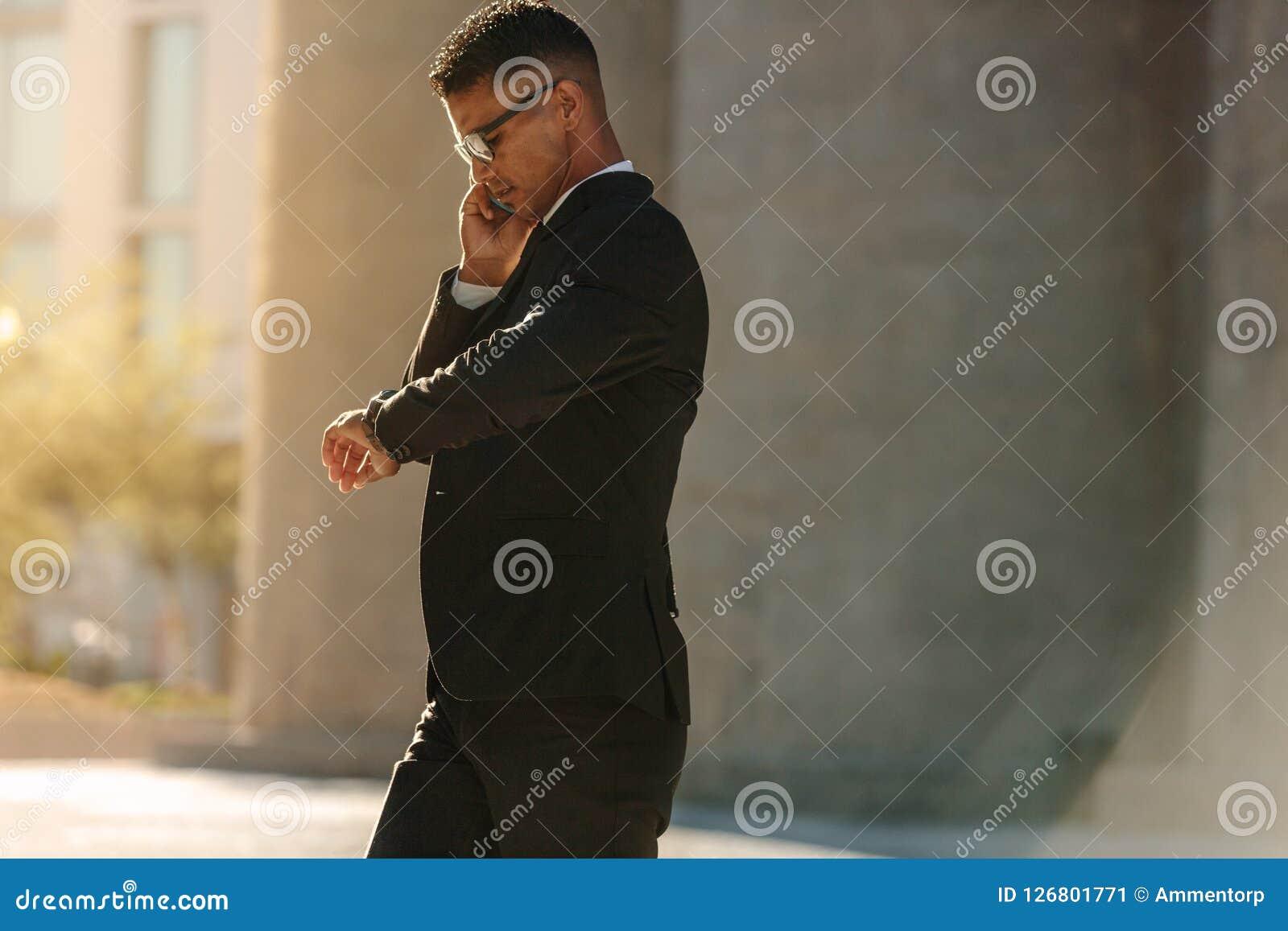 Homem que usa o telefone celular ao andar na rua