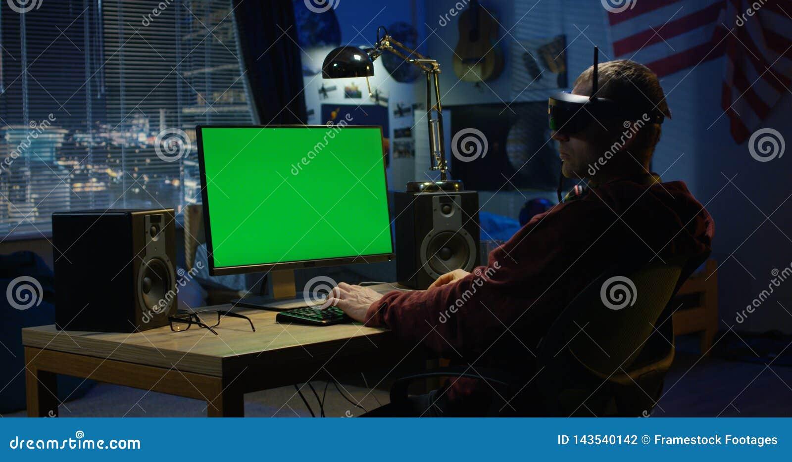 Homem que usa um computador ao vestir auriculares de VR