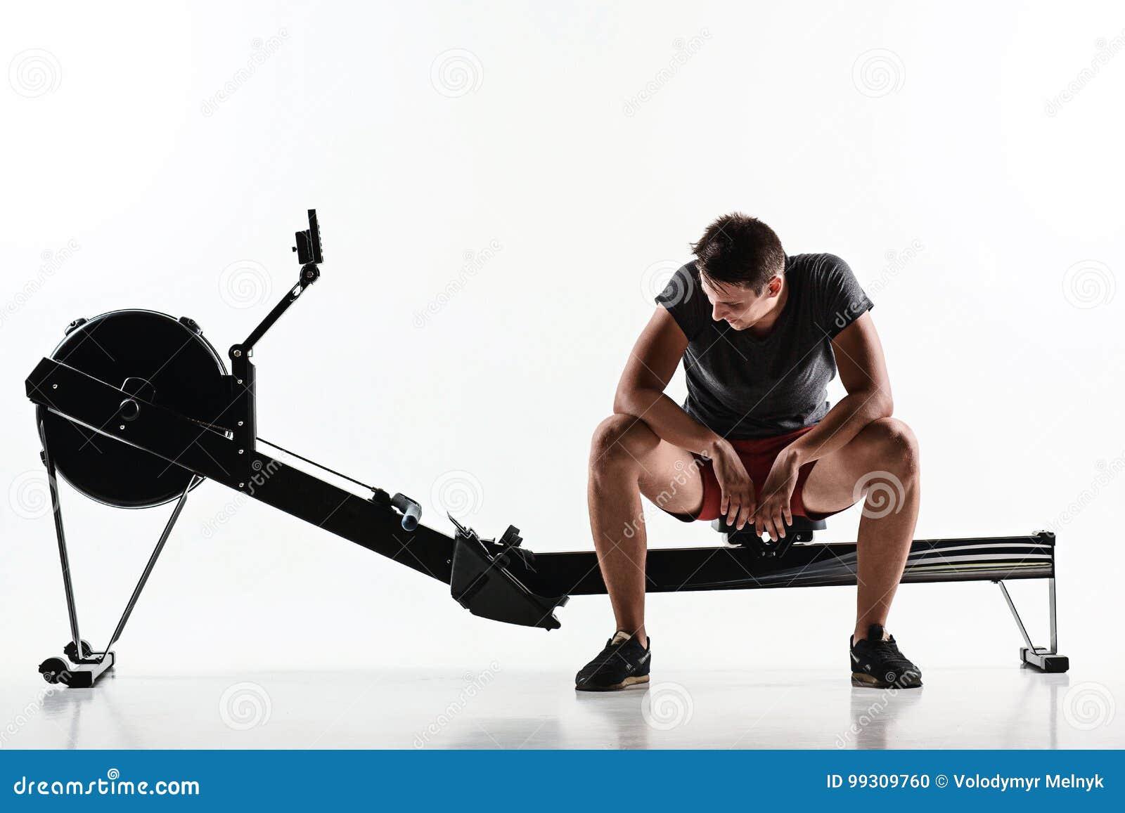 Homem que usa uma máquina da imprensa em um clube de aptidão