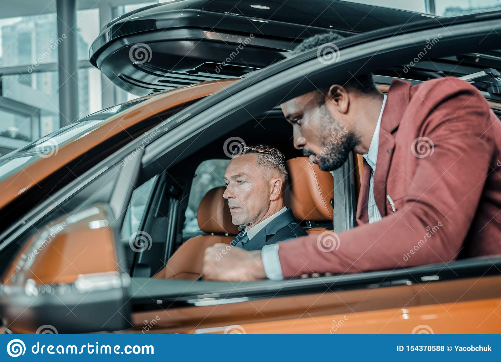 Homem sério que senta-se em um carro no salão de beleza