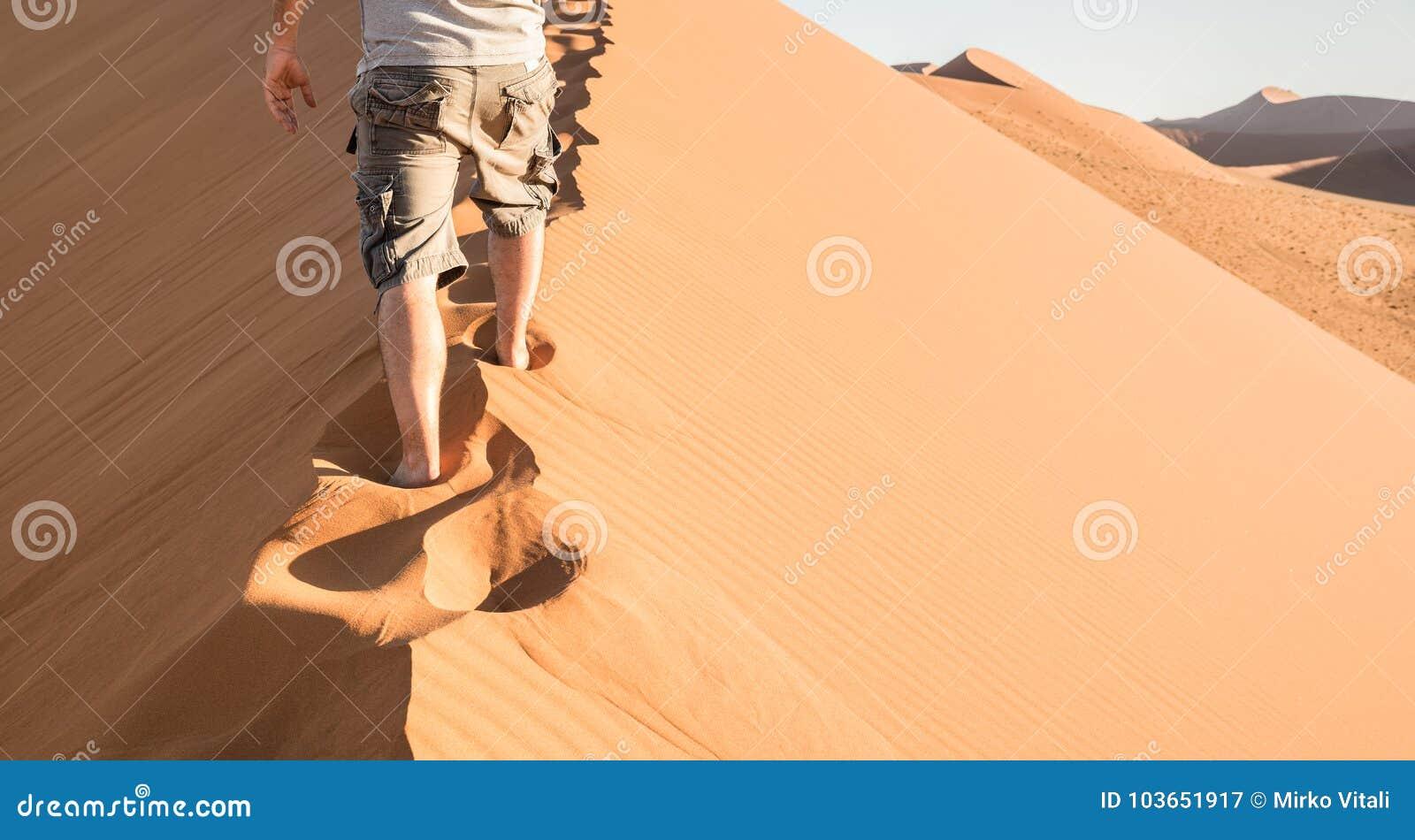 Homem só que anda na crista da areia na duna 45 no deserto de Sossusvlei