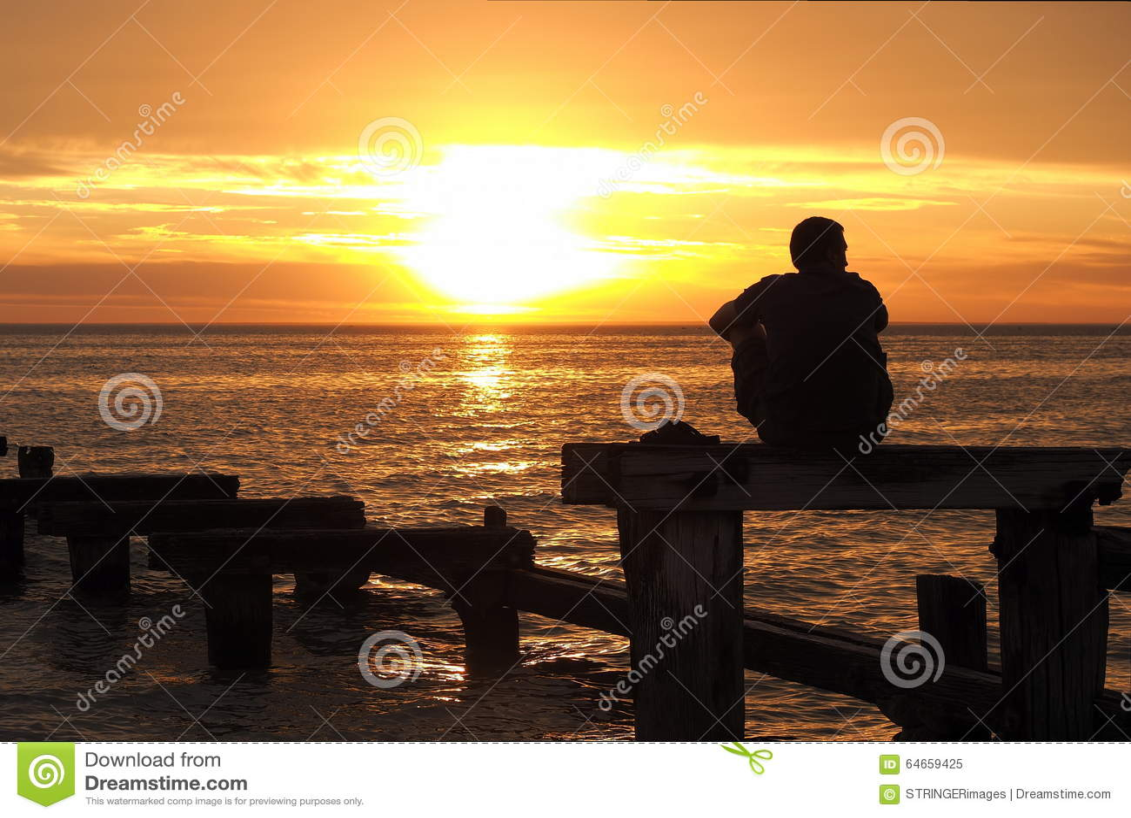 Homem só que olha o por do sol no porto Philip Bay