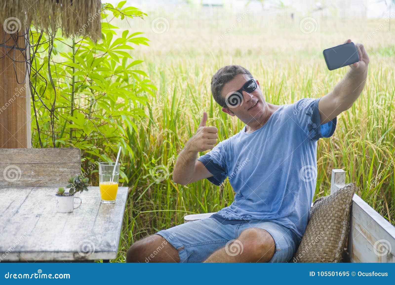 Homem 30s caucasiano atrativo novo que sorri assento feliz e relaxado na cafetaria do campo do arroz na viagem de Ásia que toma a
