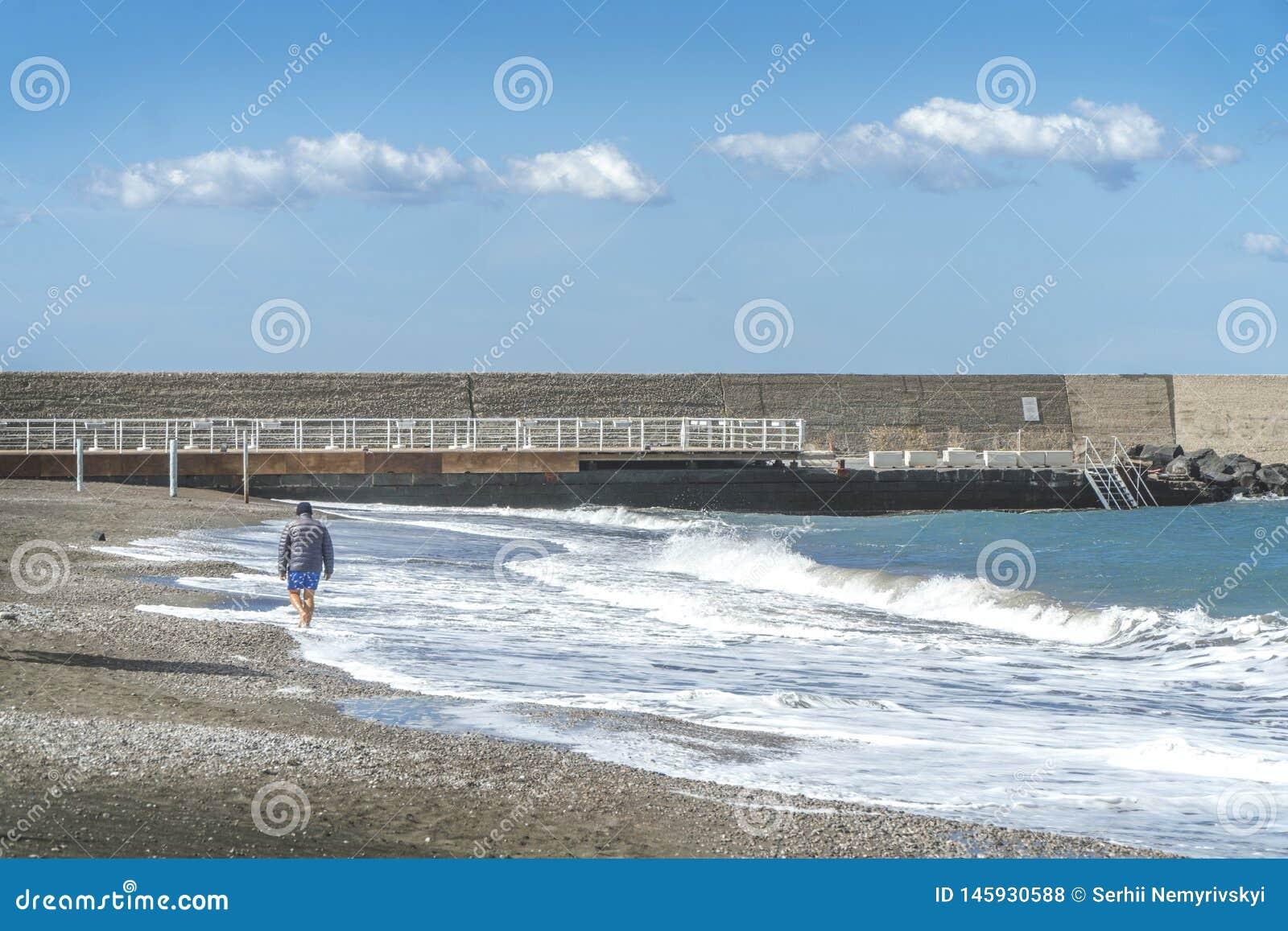 Homem s?nior que anda ao longo do trajeto pelo mar