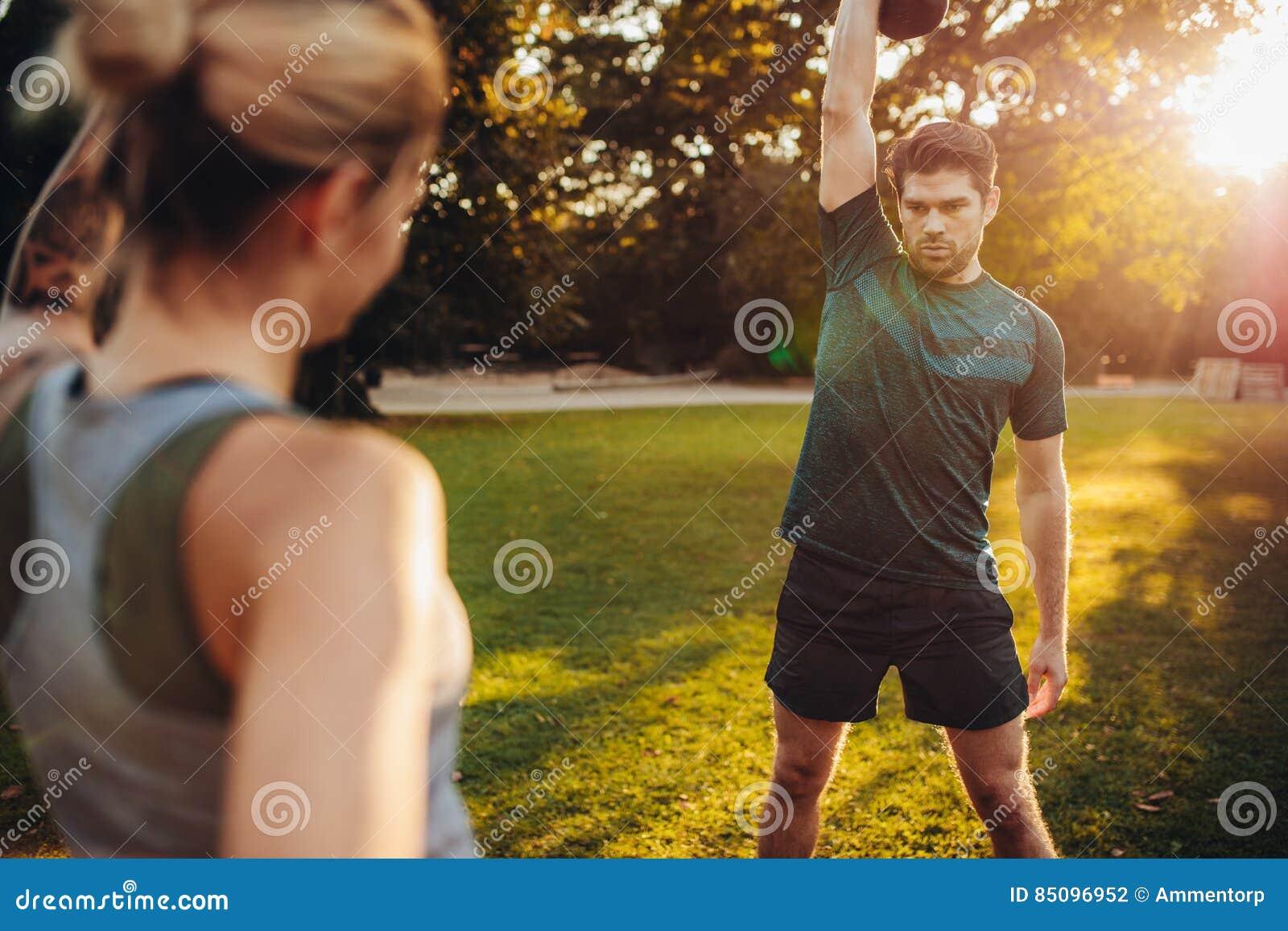 Homem saudável que exercita com o instrutor pessoal no parque