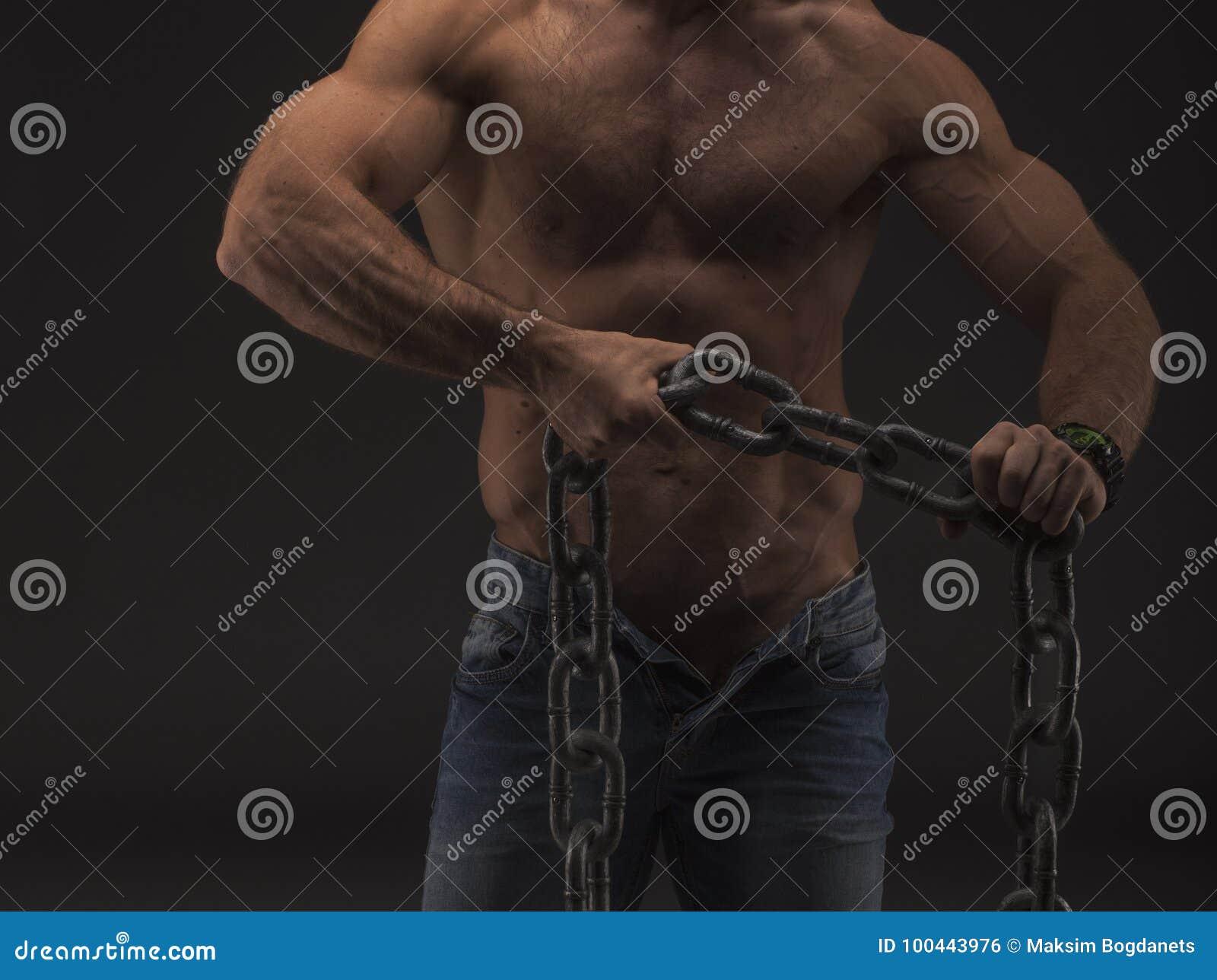 Homem  sexy  muscular com corrente grande somente nas calças de brim Corpo masculino do nude forte com veias