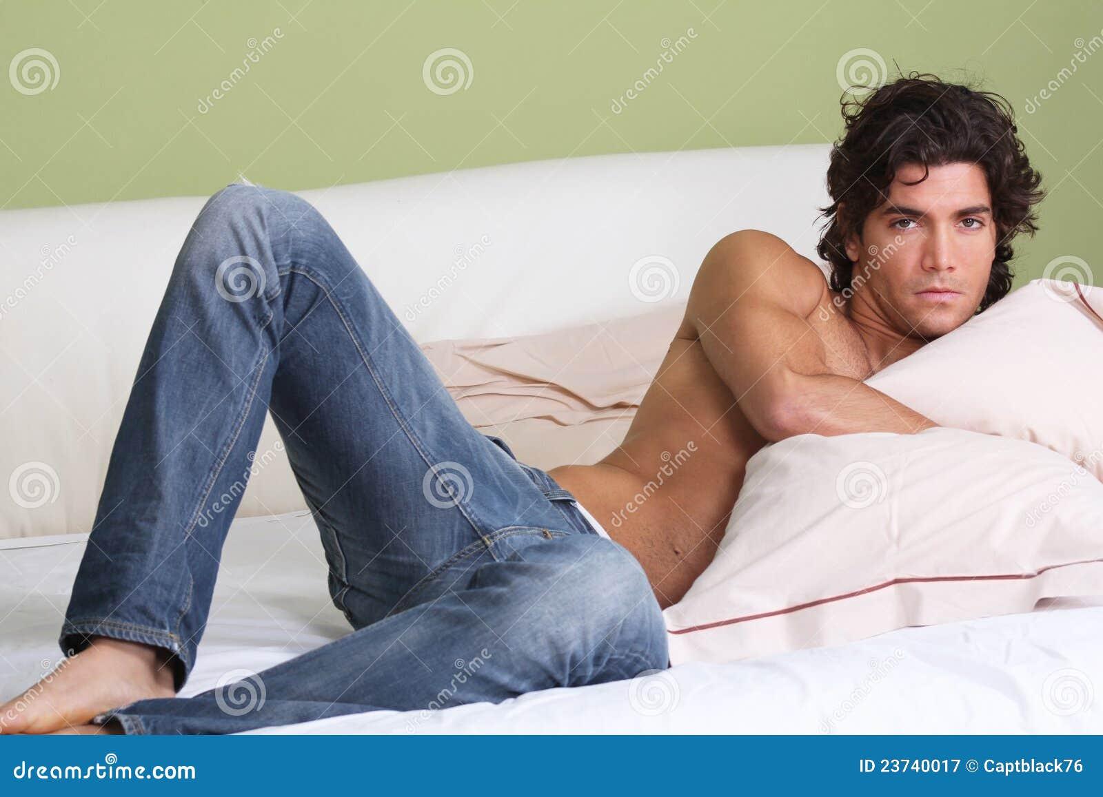 Homem  sexy  que encontra-se na cama descamisado