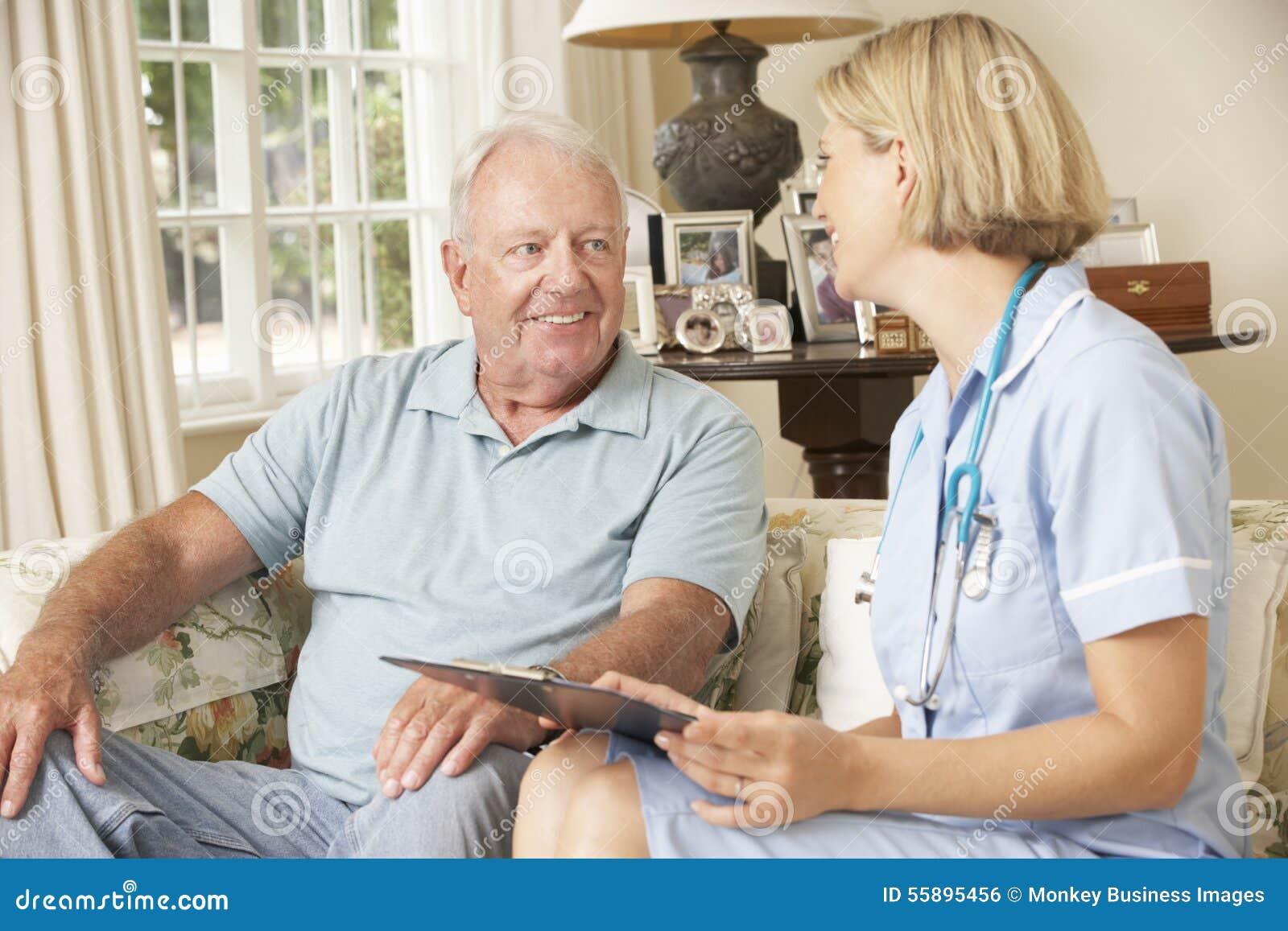 Homem superior aposentado que tem o exame médico completo com enfermeira At Home