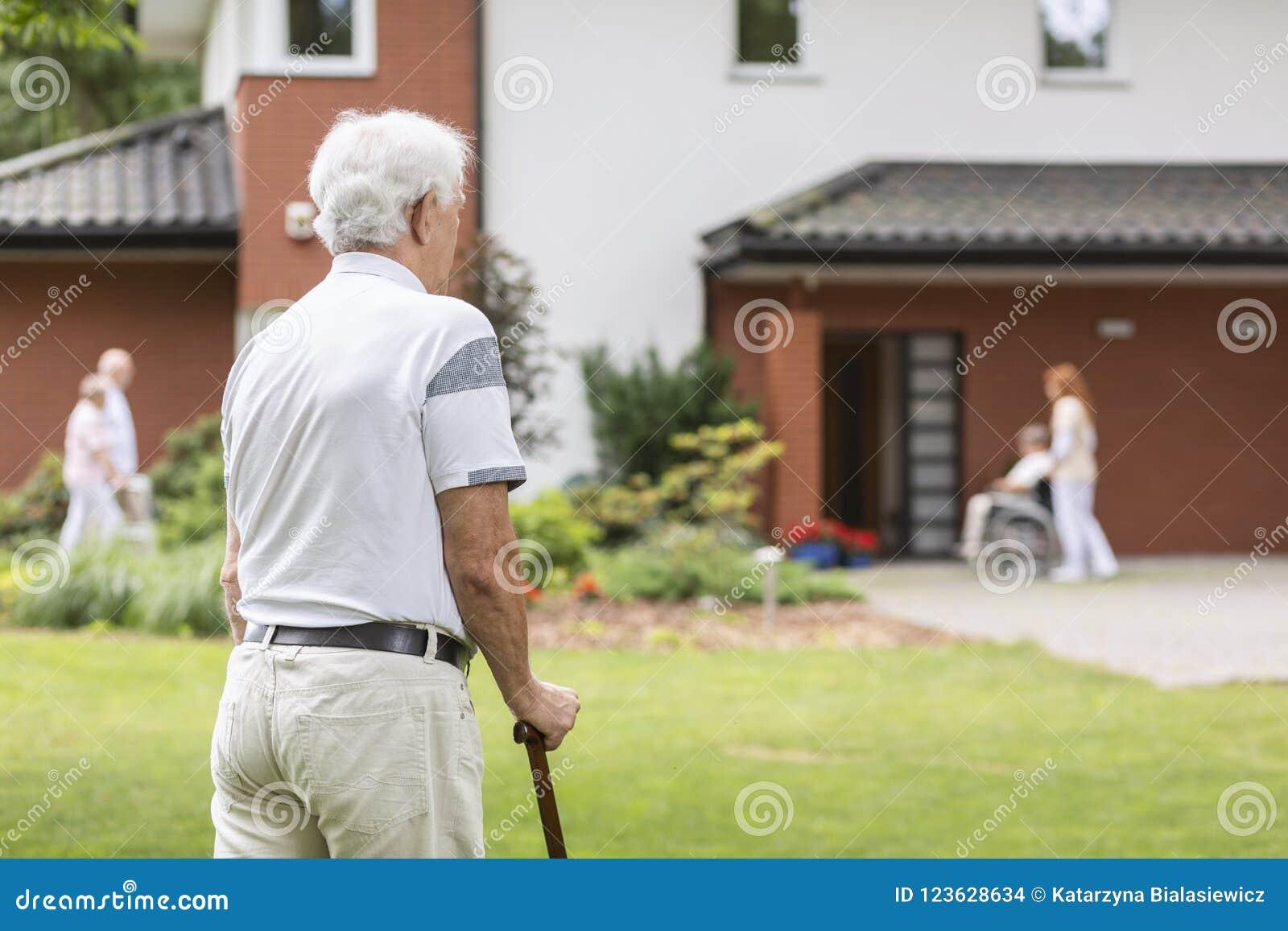 Homem superior com a vara de passeio durante a estada em uma casa dos cuidados Bl