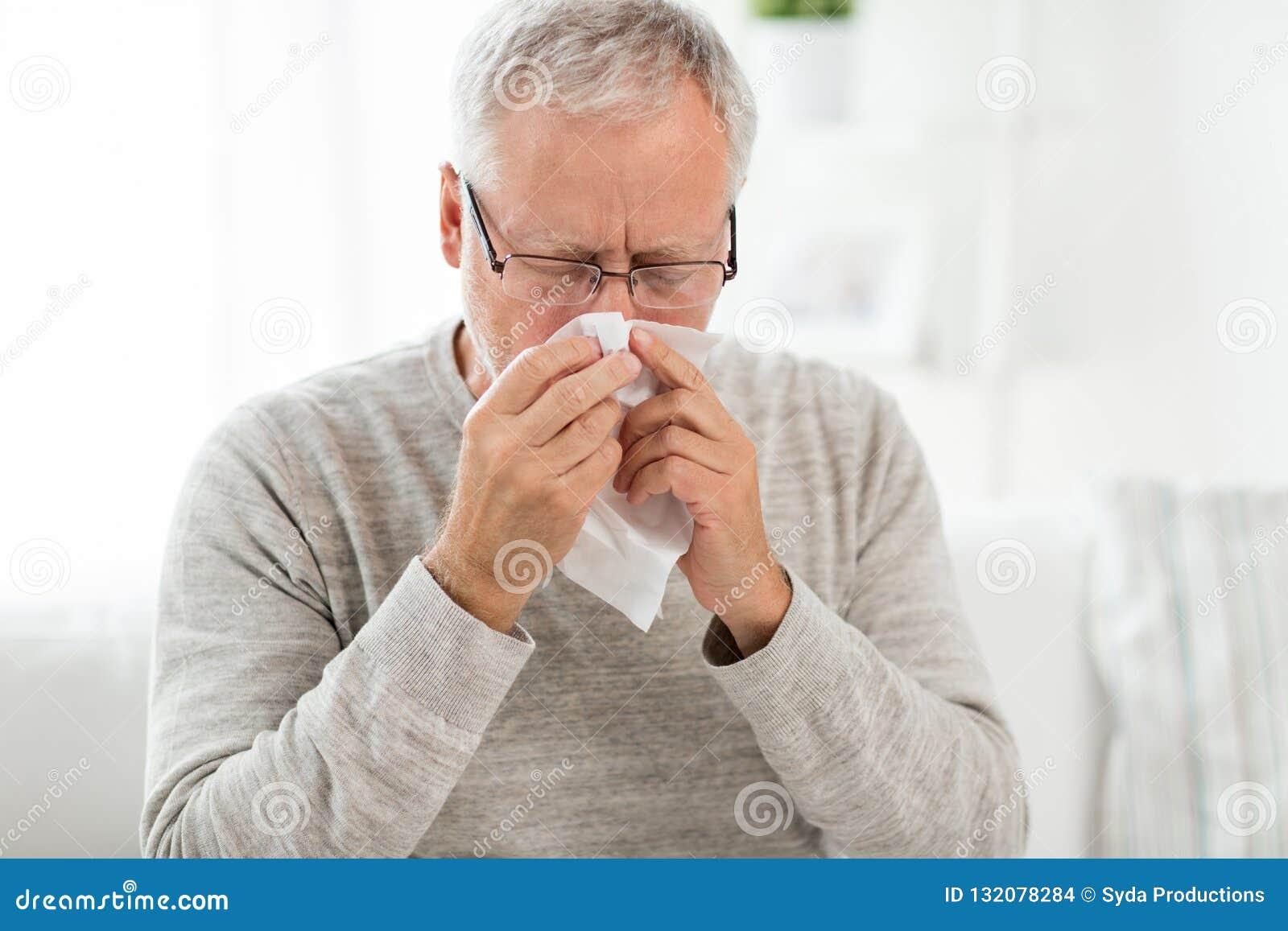 Homem superior doente com a limpeza de papel que funde seu nariz