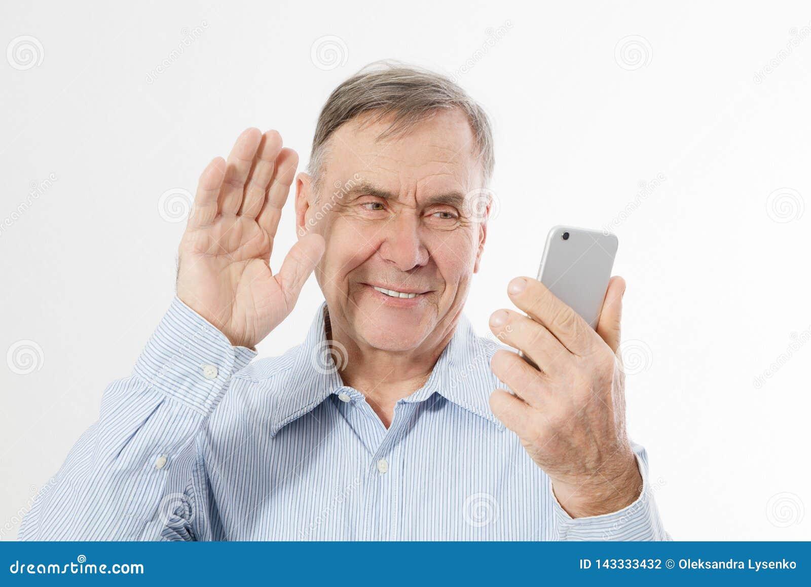 Homem superior feliz que fala no telefone no backgrpund branco O homem de negócios velho tem a conversação no bate-papo video O h