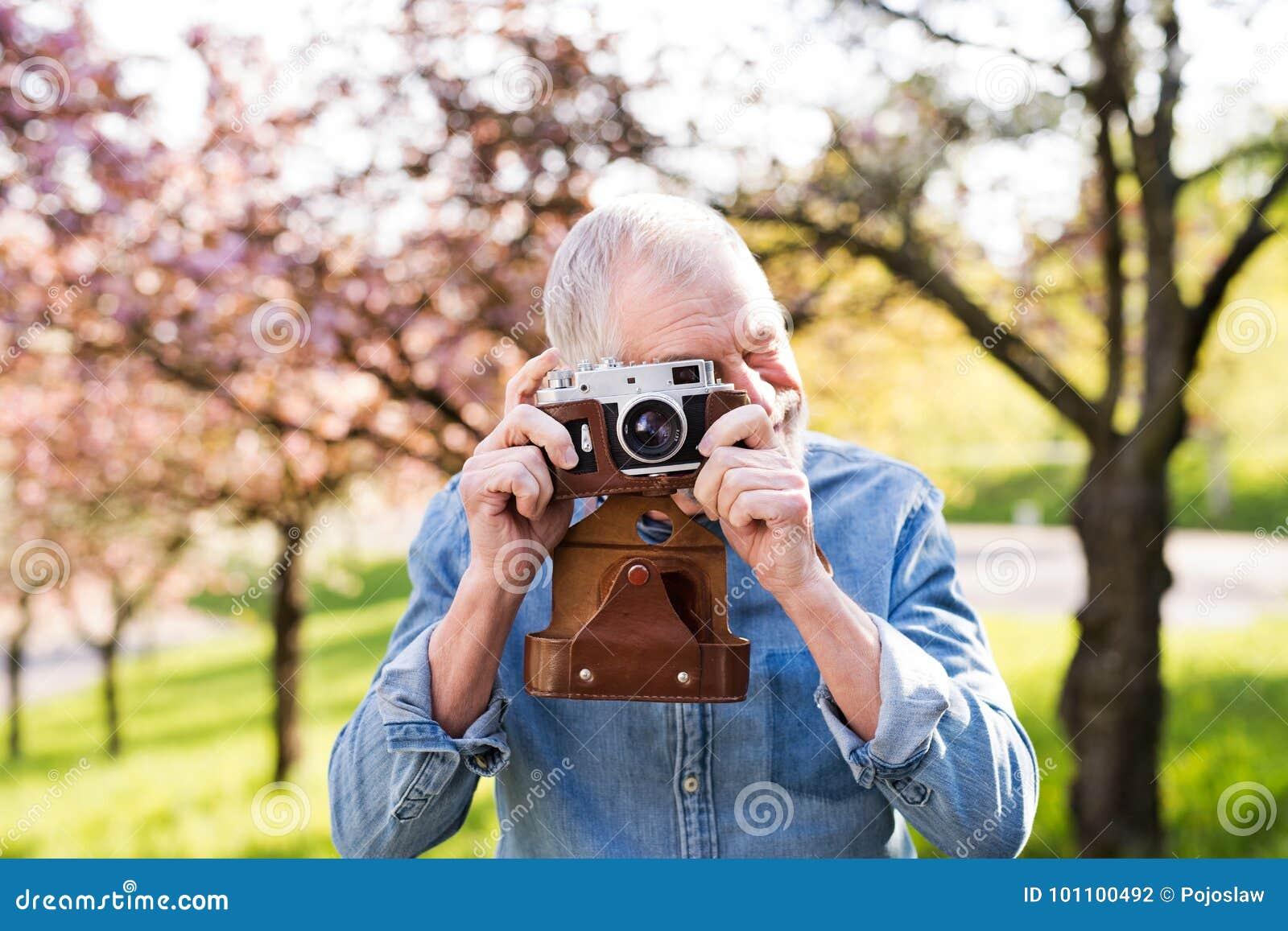 Homem superior fora na natureza da mola que toma imagens