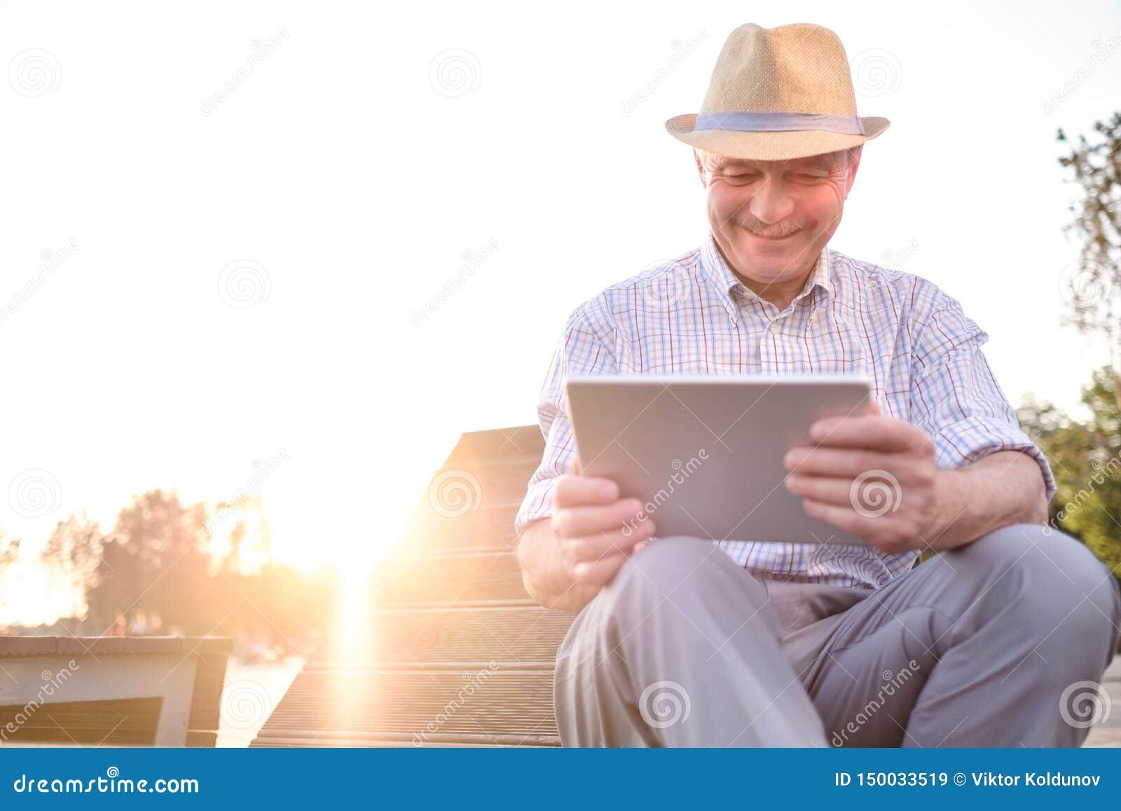 Homem superior latino-americano na tabuleta da leitura do chapéu do verão no espaço da cópia do parque