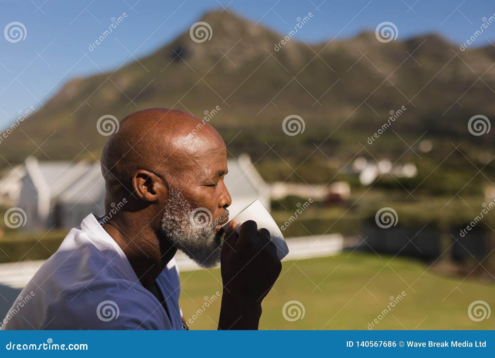 Homem superior que come o café no balcão