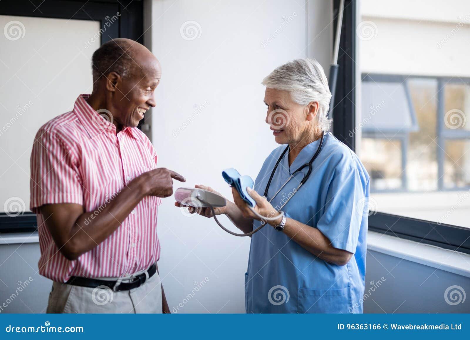 Homem superior que fala para medicar ao apontar na pressão sanguínea