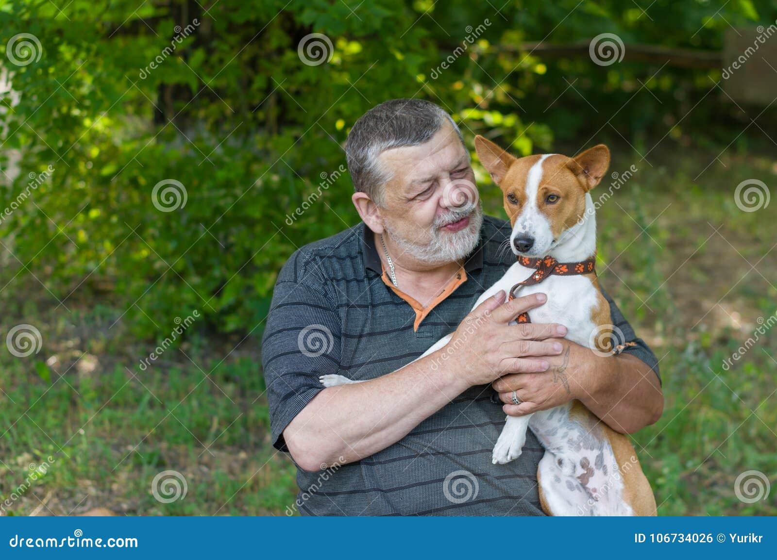 Homem superior que fala a seu basenji bonito do cão que toma o nas mãos ao descansar no parque do verão
