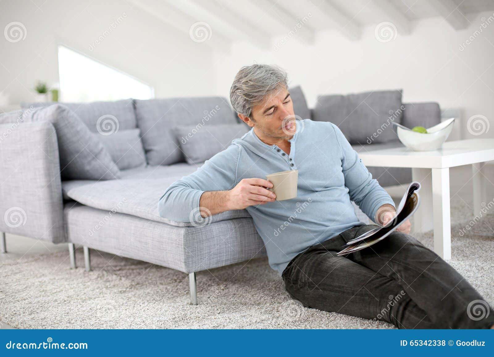 Homem superior que relaxa em casa lendo o compartimento