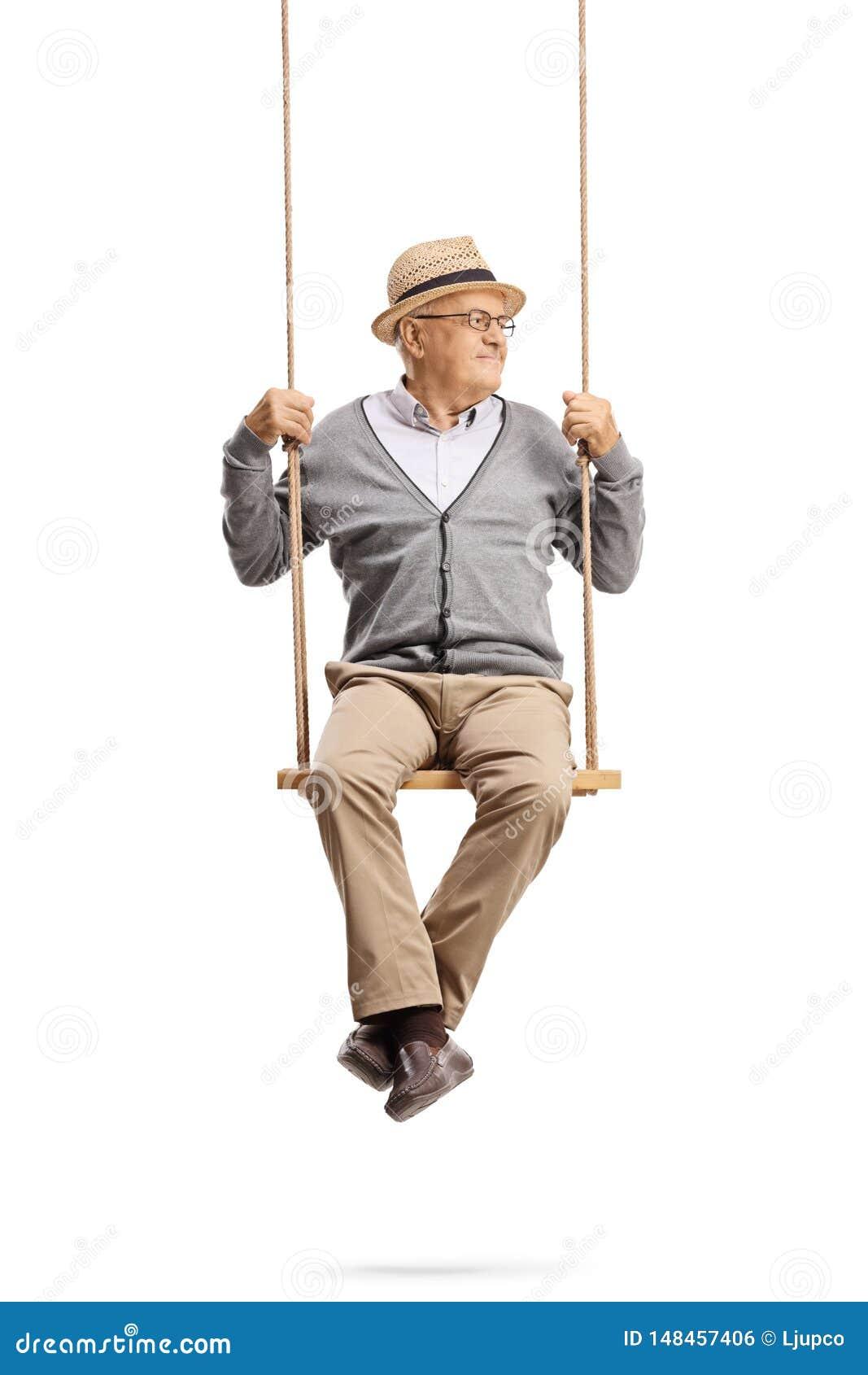 Homem superior que senta-se em um balanço e que olha afastado
