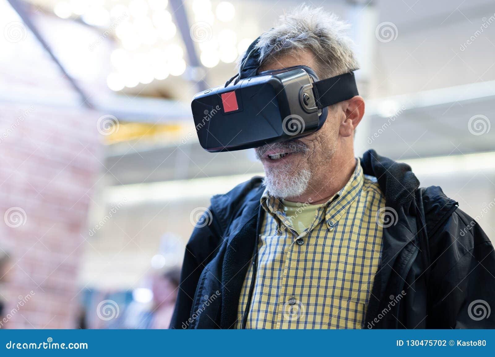 Homem superior que veste os óculos de proteção da realidade virtual que olham a apresentação da realidade virtual
