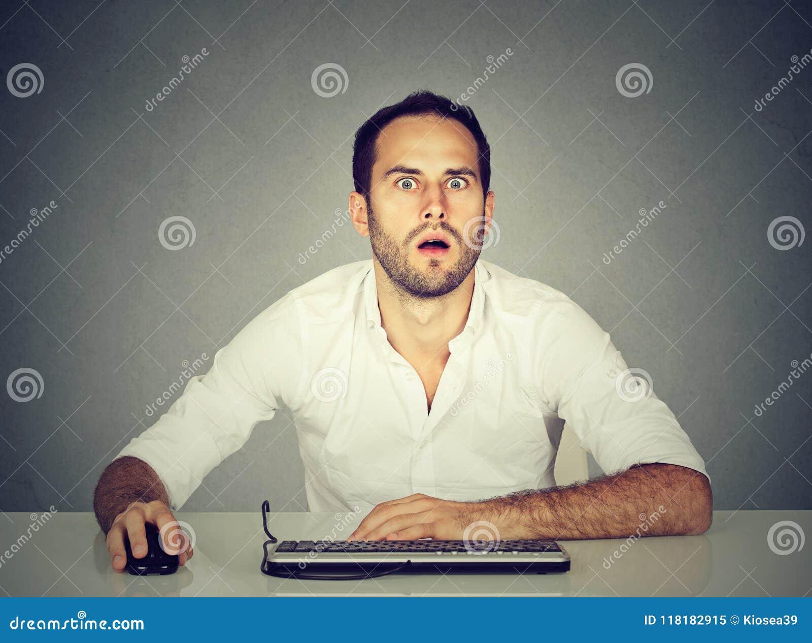 Homem surpreendido que usa o computador na mesa