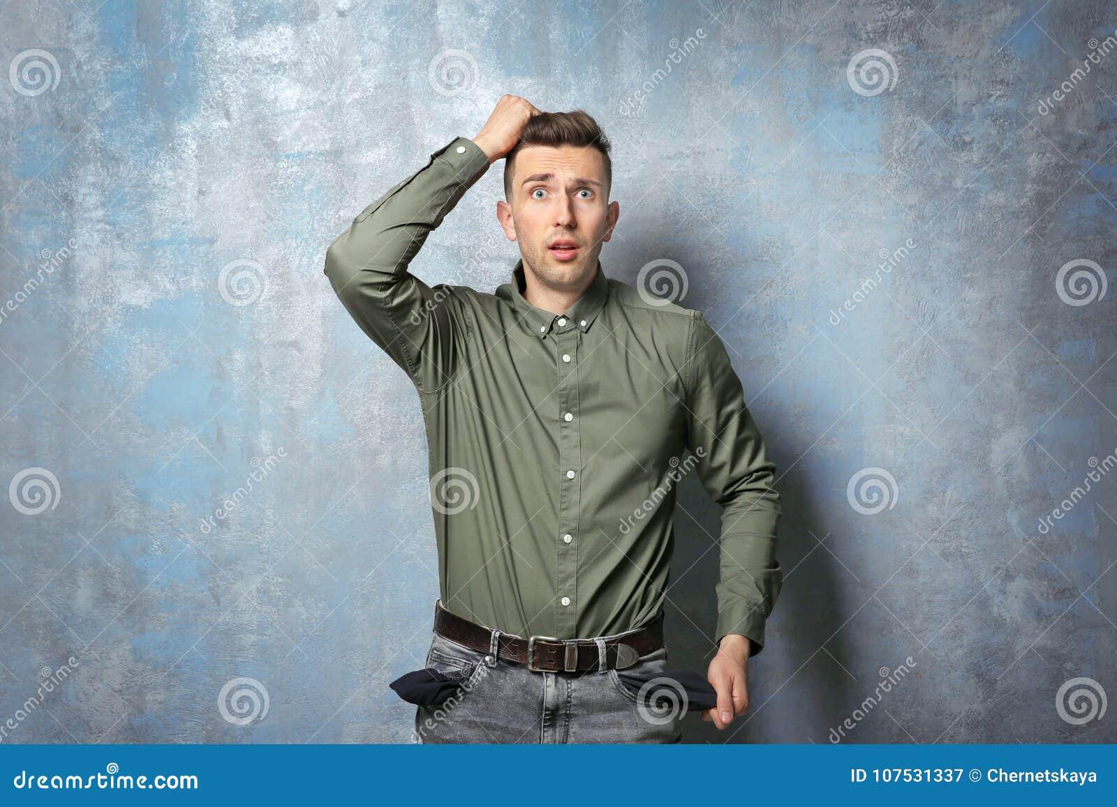 Homem triste que mostra seus bolsos vazios