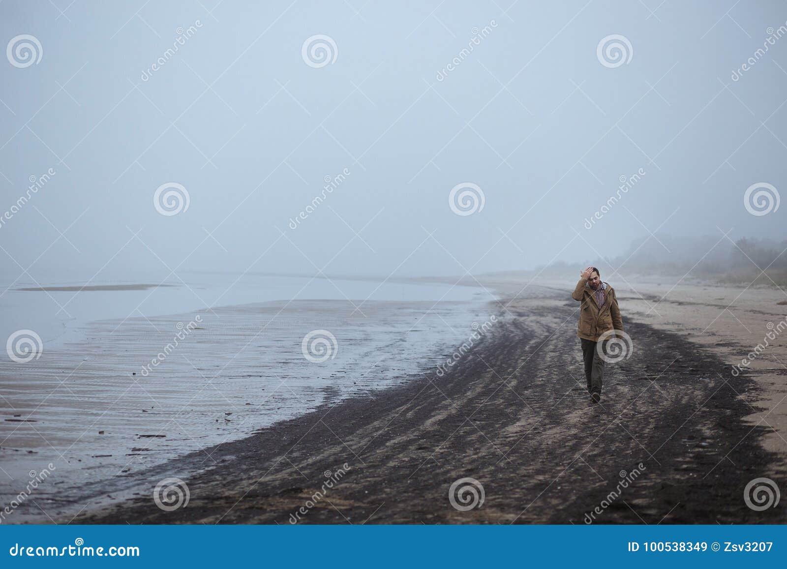 Homem triste só que anda em uma praia nevoenta