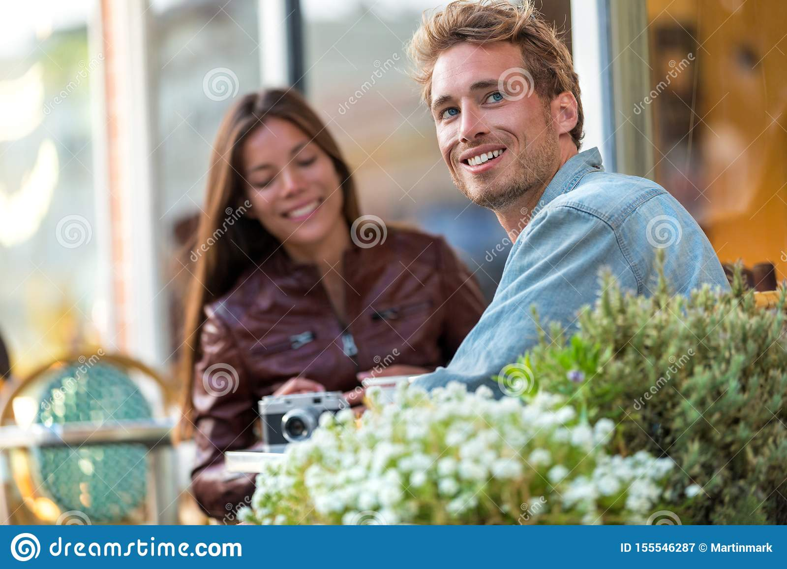 Homem urbano novo que aprecia o assento na tabela do restaurante com o amigo na cidade Férias europeias dos pares do curso Estilo