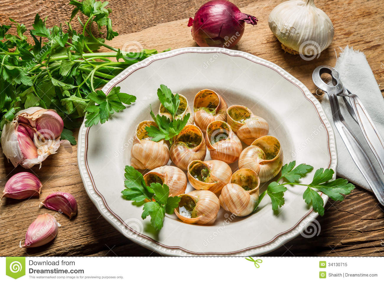 Homemade baked snails with garlic butter and fresh herbs on old wooden ...