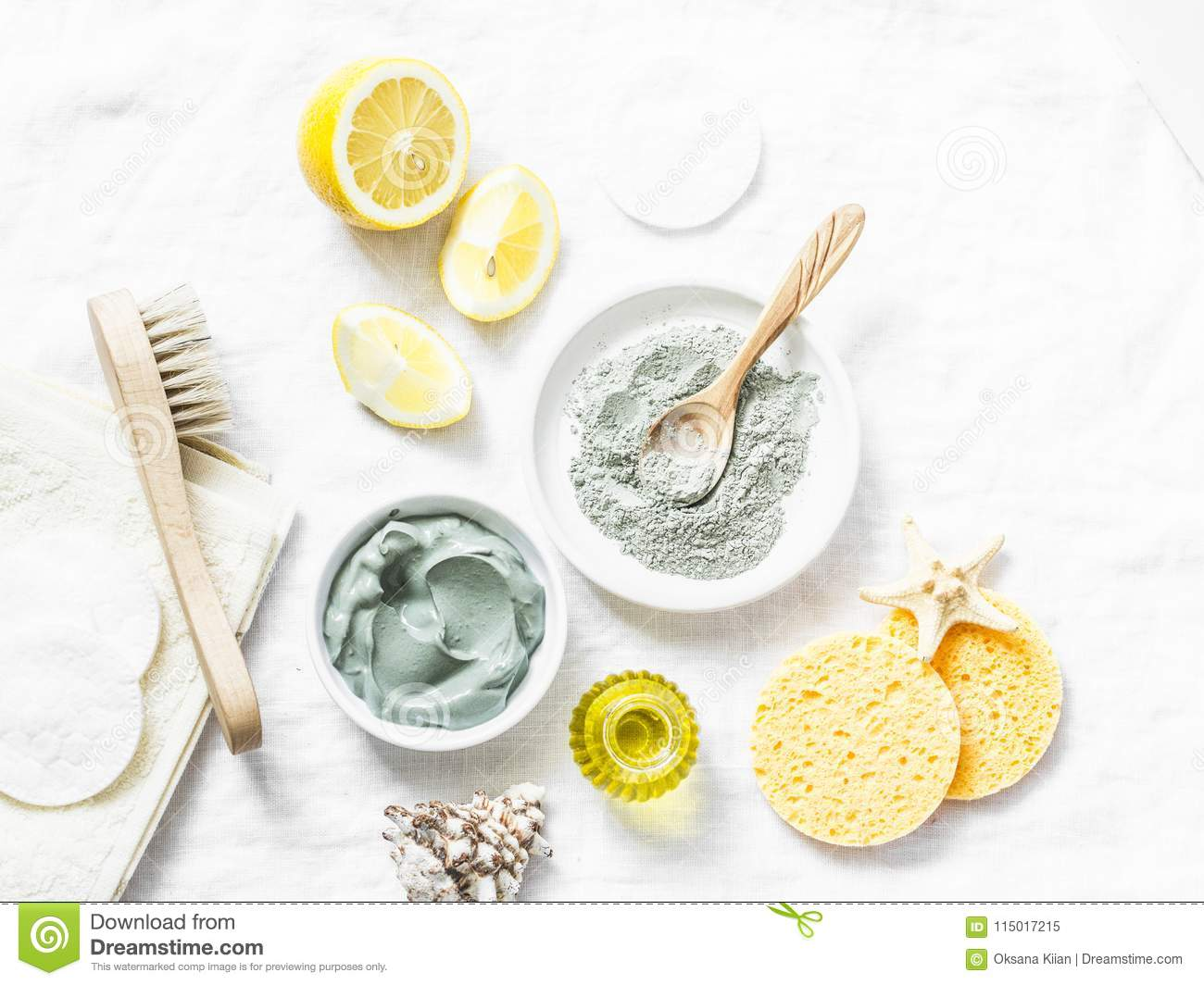 Homemade beauty facial mask. Clay, lemon, oil, facial brush - beauty products ingredients on light background