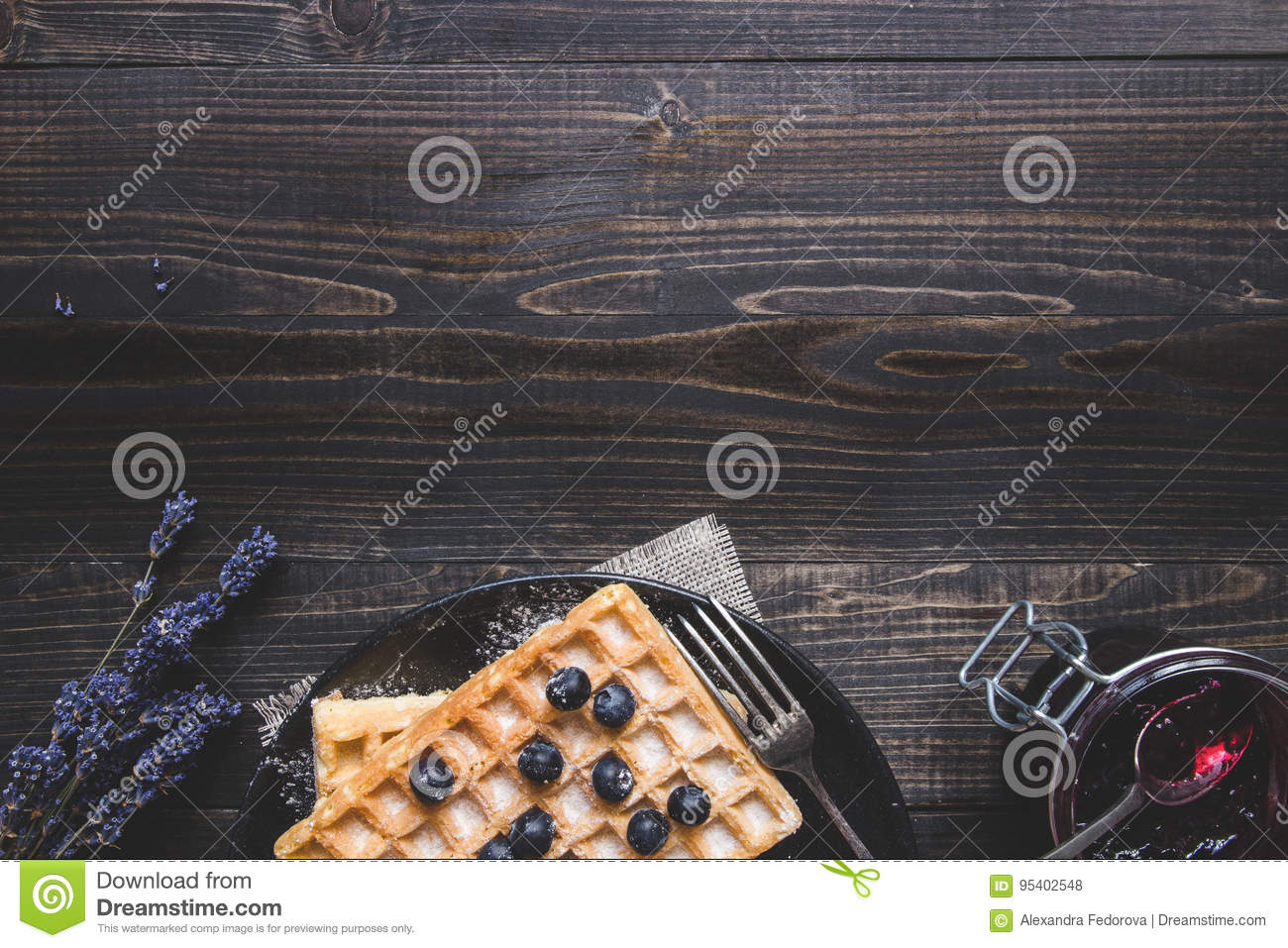 Homemade belgian waffles with blueberries on the dark wooden table with copy space