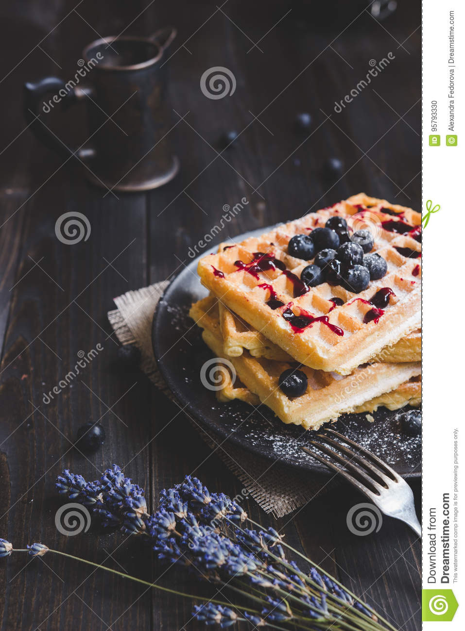 Homemade belgian waffles with blueberries and jam on the dark wooden table