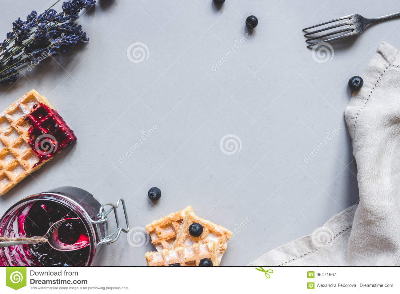 Homemade belgian waffles with blueberries and jam on the light blue table with copy space