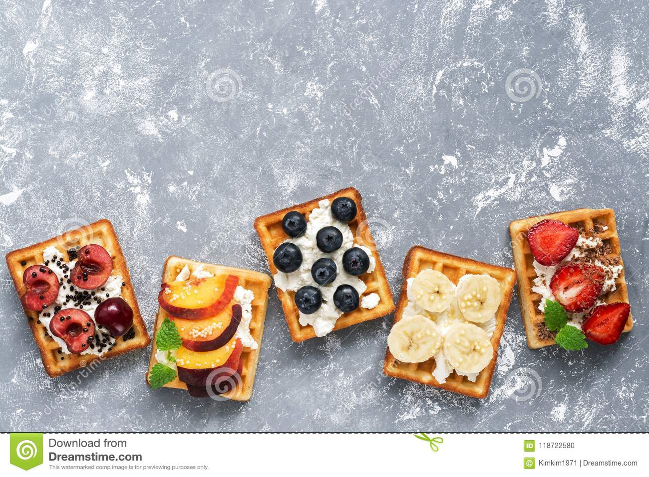Homemade Belgian waffles with a variety of fruits on a gray background. Top view, copy space.