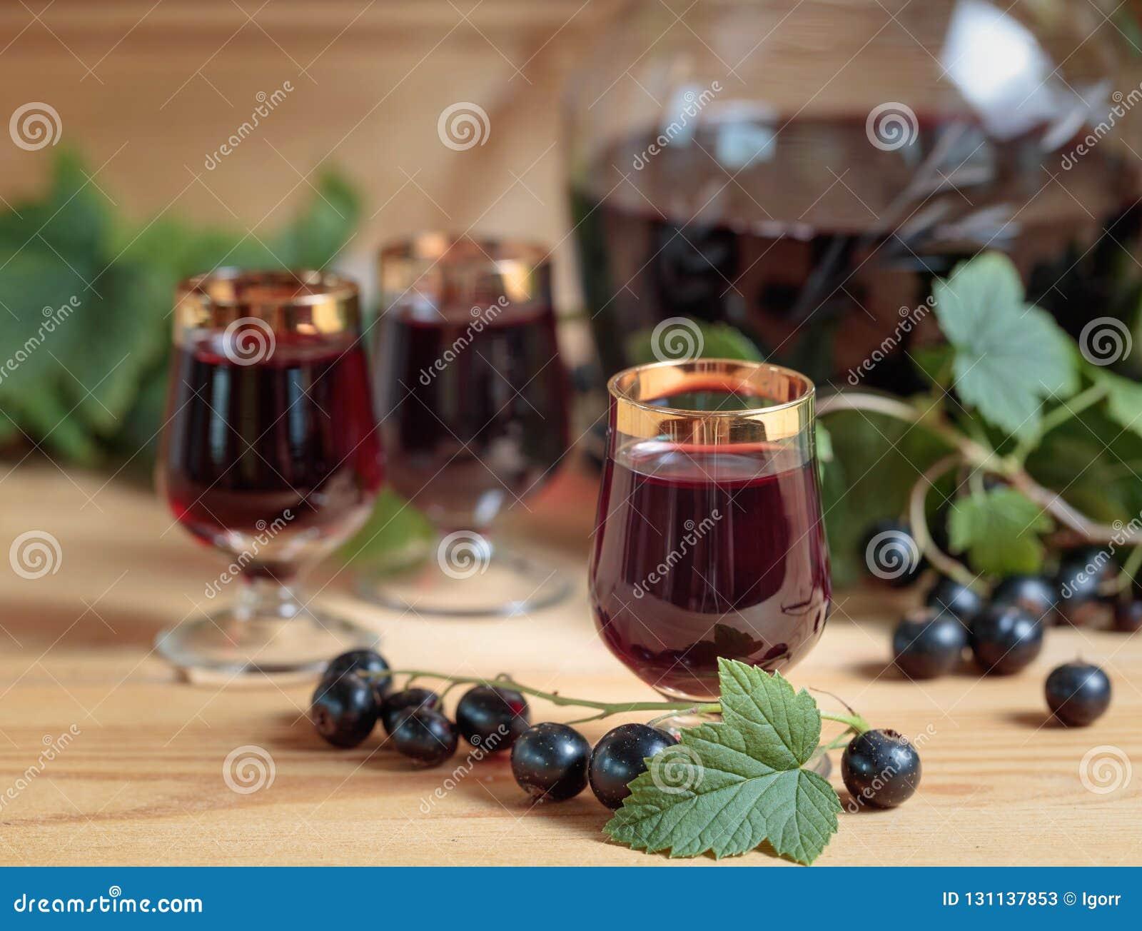 Homemade black currant liqueur and fresh berries .
