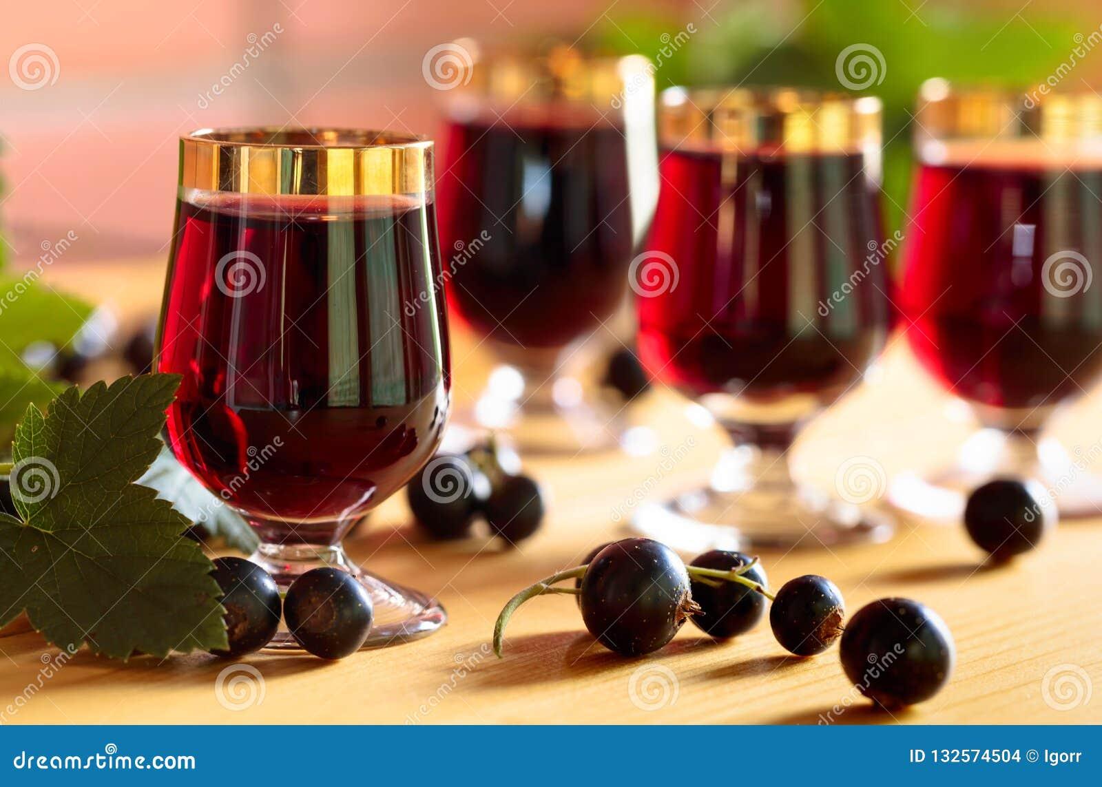 Homemade black currant liqueur and fresh berries