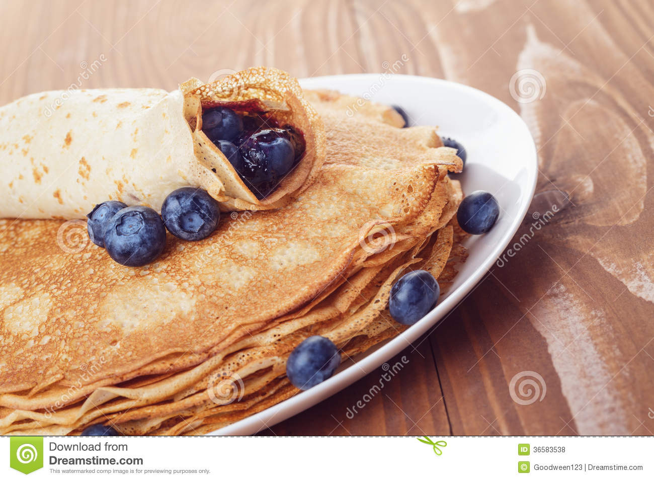 Homemade blinis or crepes with blueberries and jam toned photo