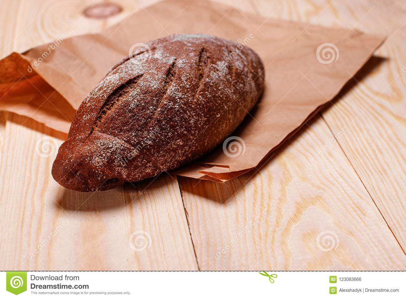 Homemade bread on paper bag. Baked product on wooden table. Close view