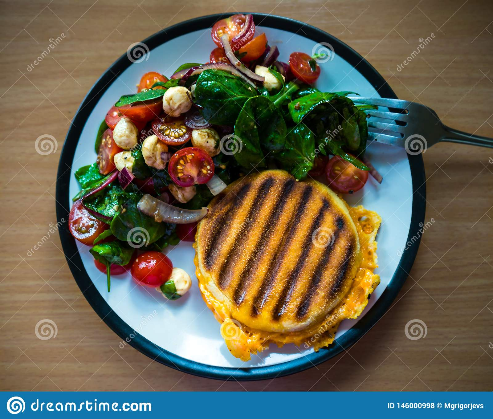 Homemade Breakfast grilled English miffin Sandwich served with side salad: cherry tomatoes, pearl mozzarella and spinach