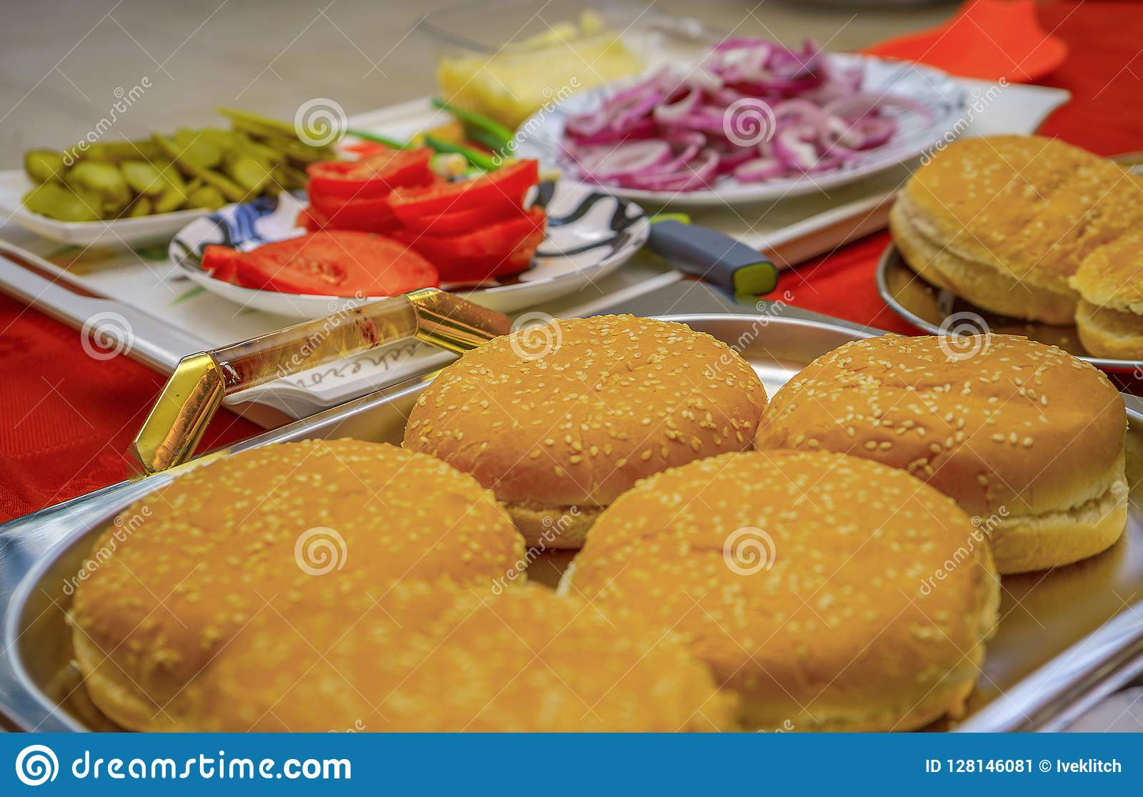 Homemade burger ingredients arranged on tray and plates outdoors. Onion, salted cucumbers, cherry tomatoes, ketchup sauce.