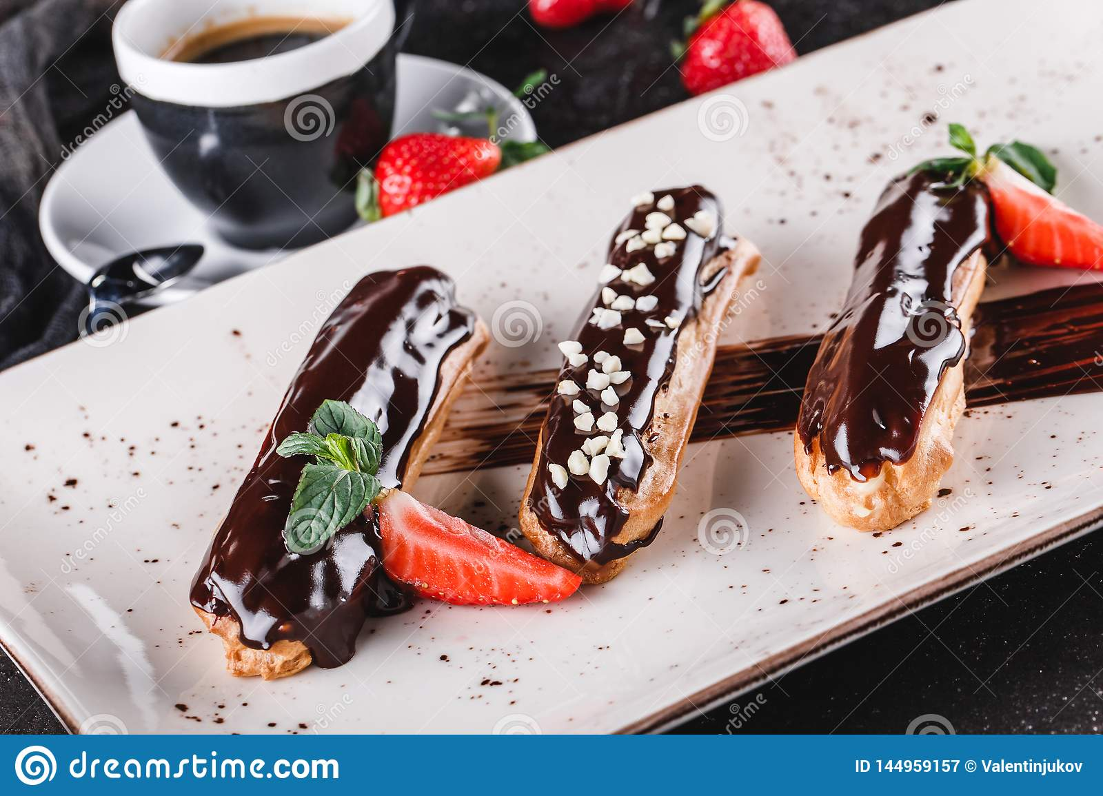 Homemade cake eclairs or profiteroles with custard, chocolate and strawberries on dark background served with cup of coffee